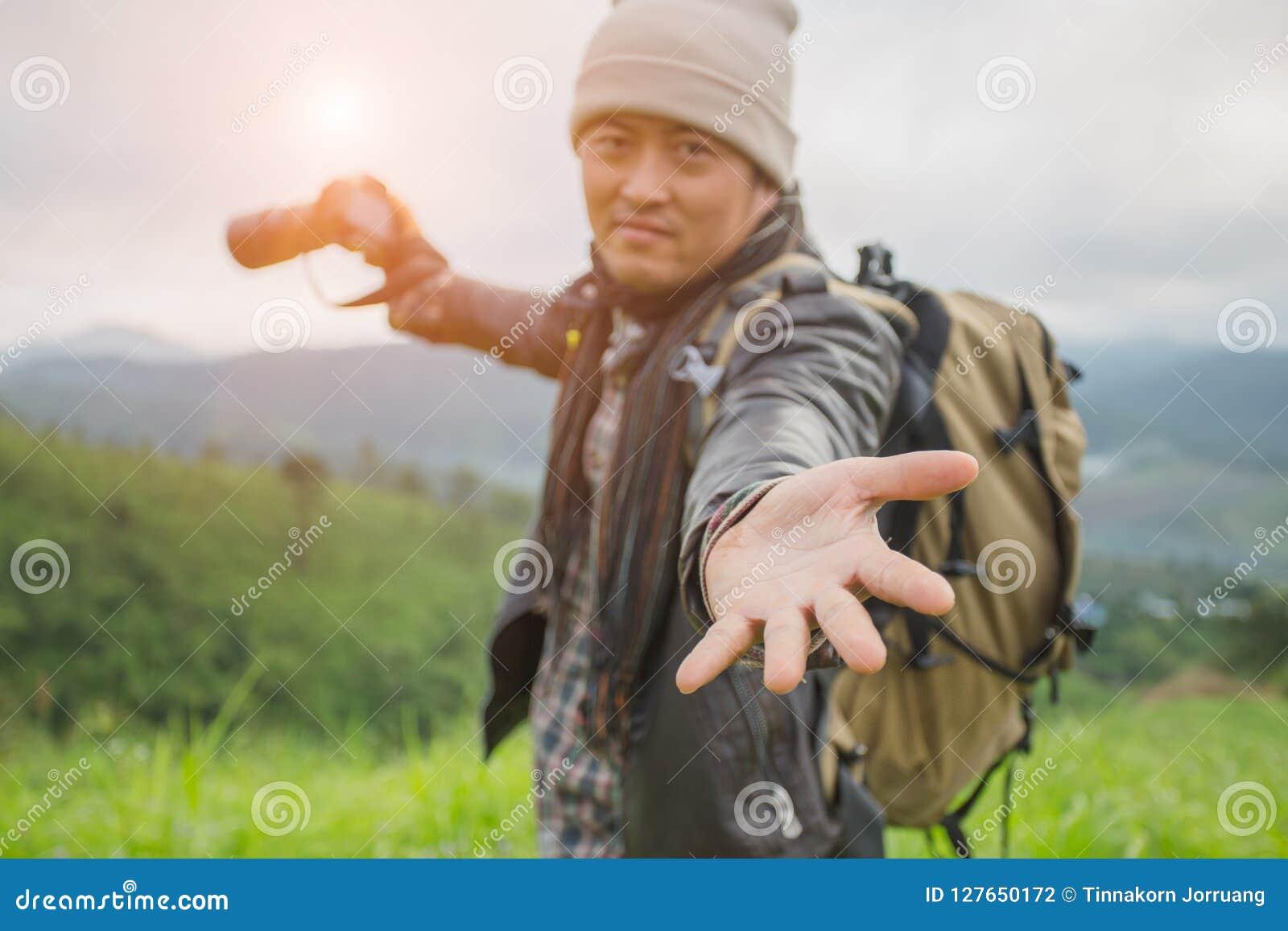 Турист с рюкзаком на наклоне горы с поднятыми руками сверх,