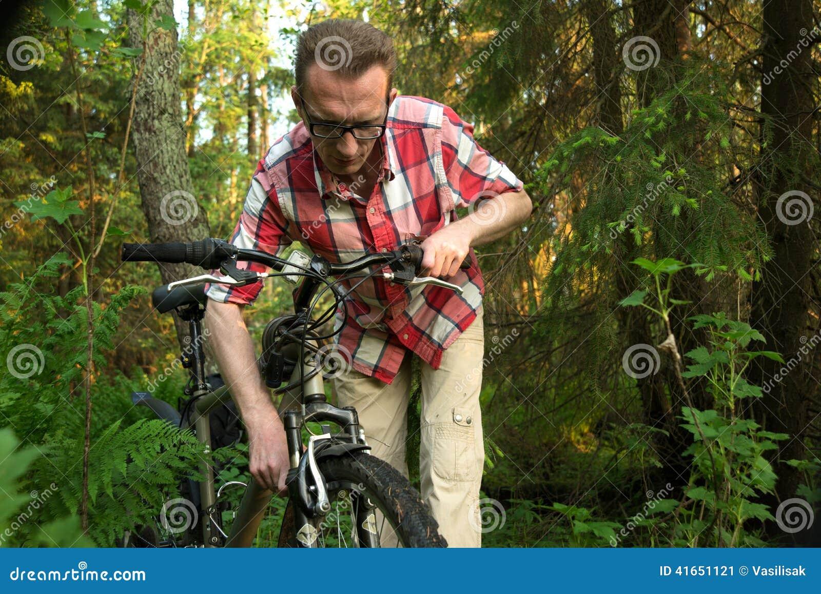 Турист, repearing велосипед в древесинах