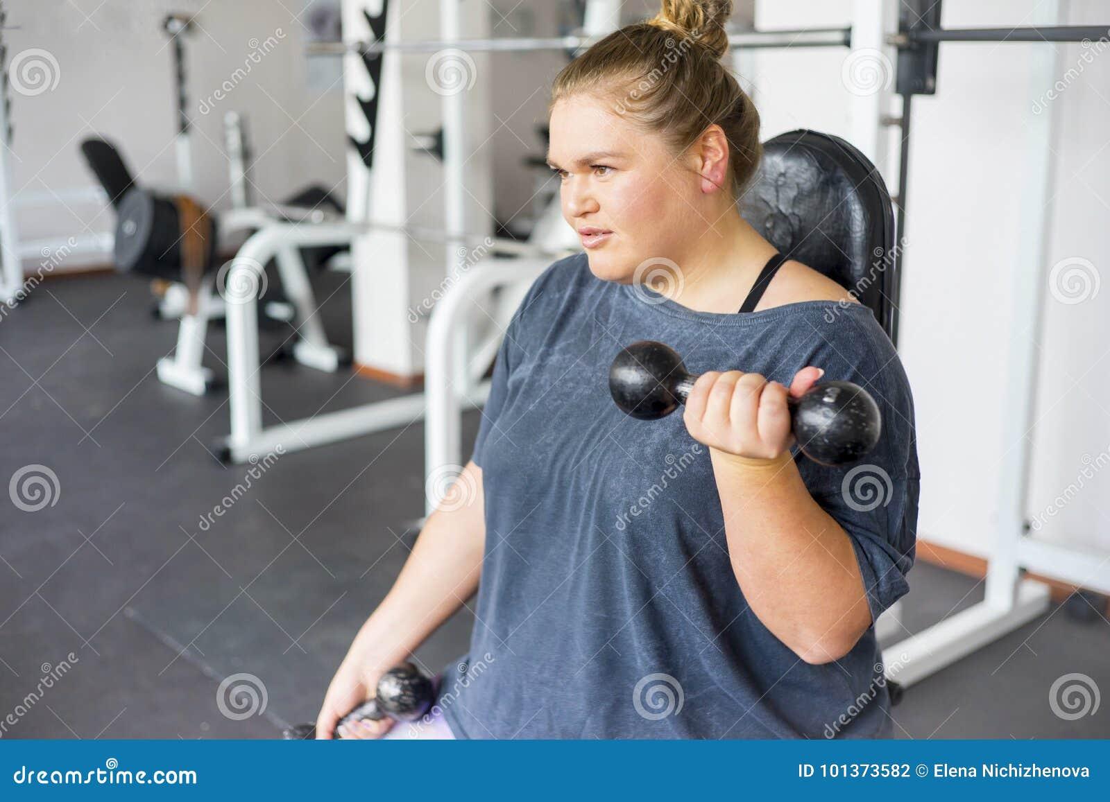 Тучная девушка в спортзале