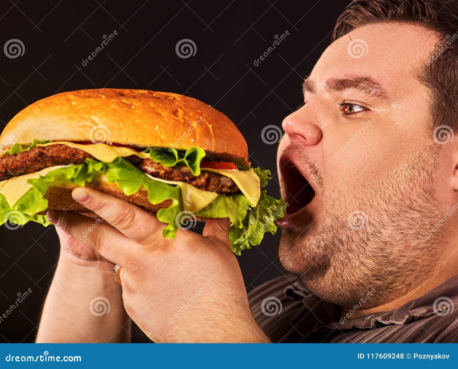 Тучный человек есть hamberger фаст-фуда Завтрак для полной персоны