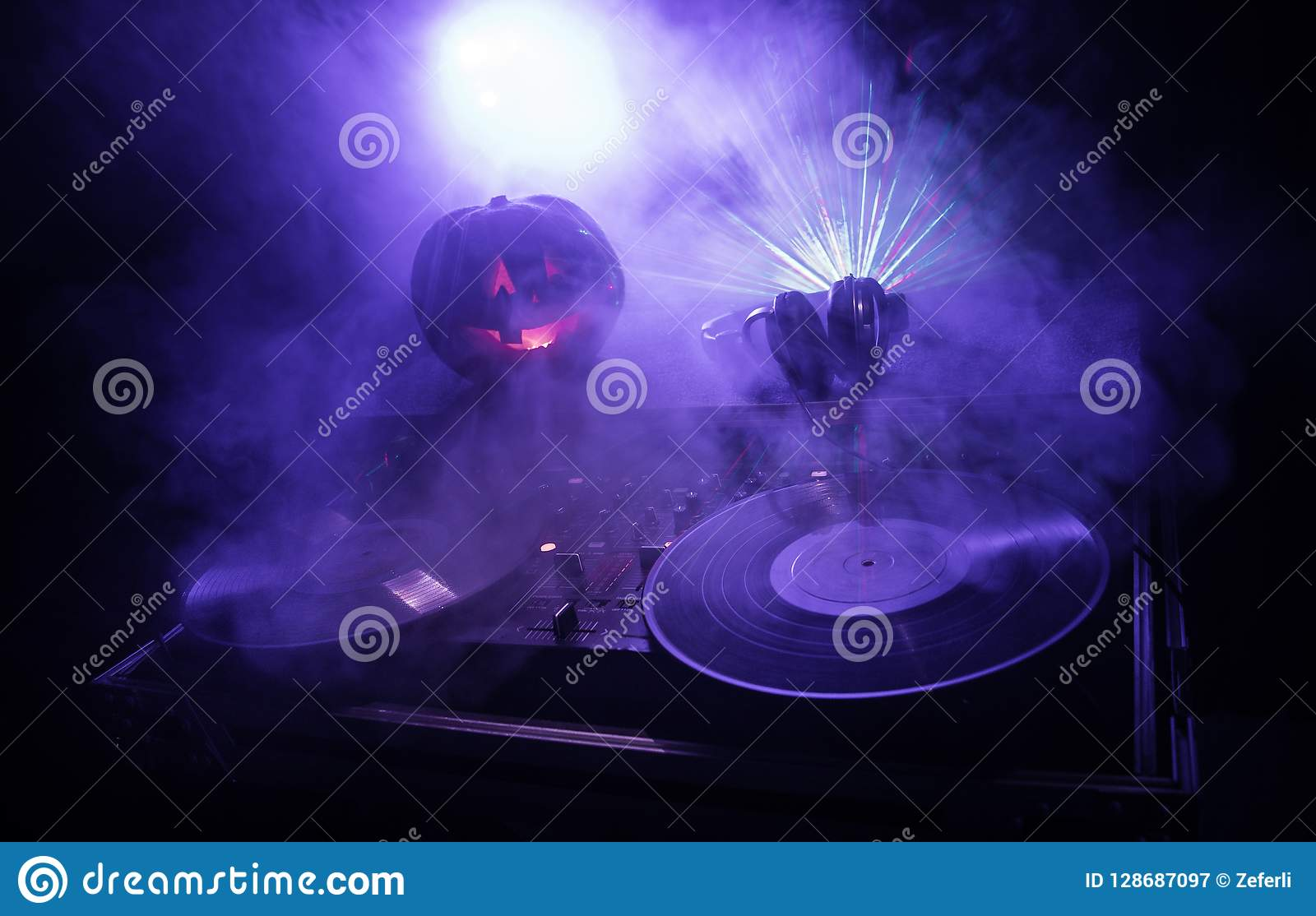 Тыква хеллоуина на таблице dj с наушниками на темной предпосылке с космосом экземпляра Счастливые украшения и музыка фестиваля хе