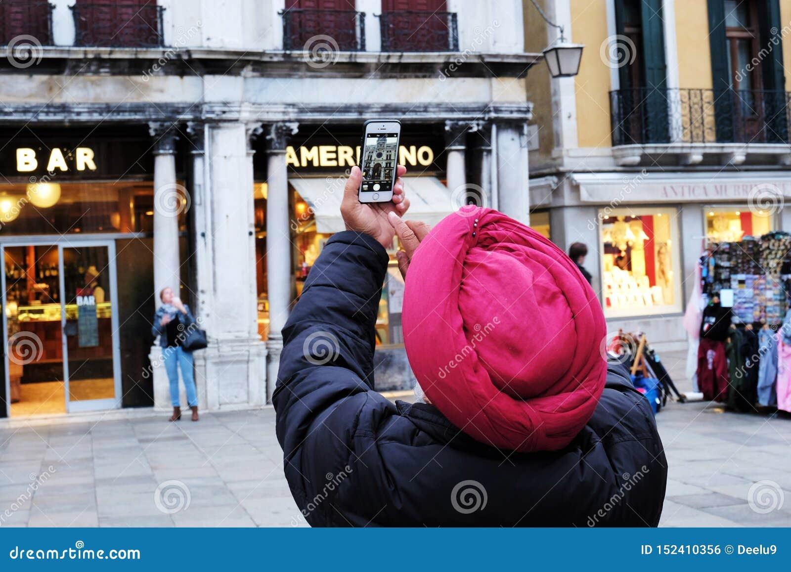 Тюрбан человека нося принимая фото башни с часами в аркаде Сан Marco в Венеции, Италии