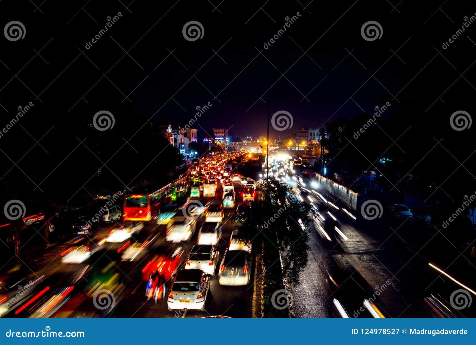 Тяжелое автомобильное движение в центре города Дели, Индии на ноче