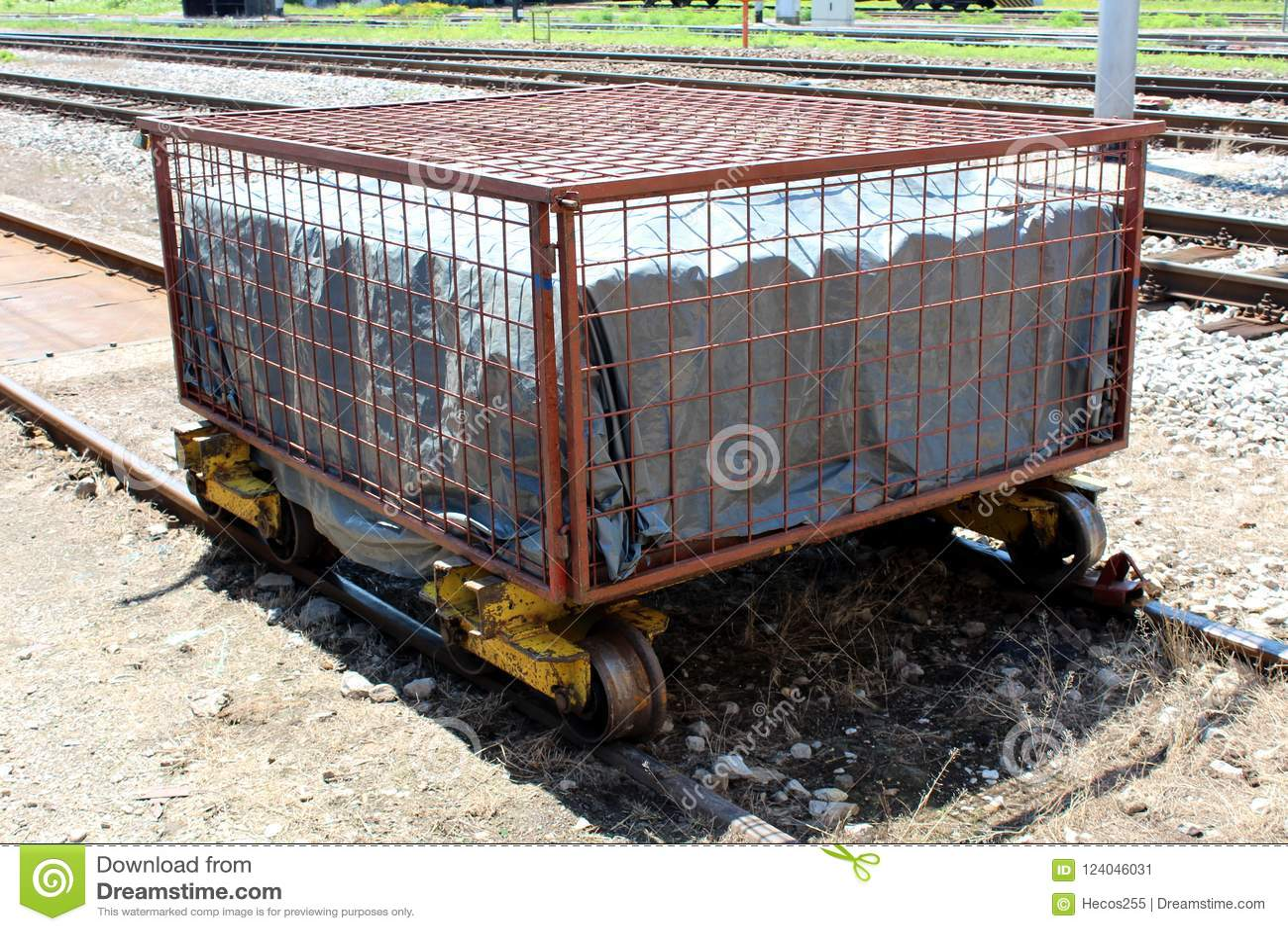 Тяжело - используемая заржаветая тележка металла железнодорожная закрытая с сильной клеткой провода на неиспользованной части жел