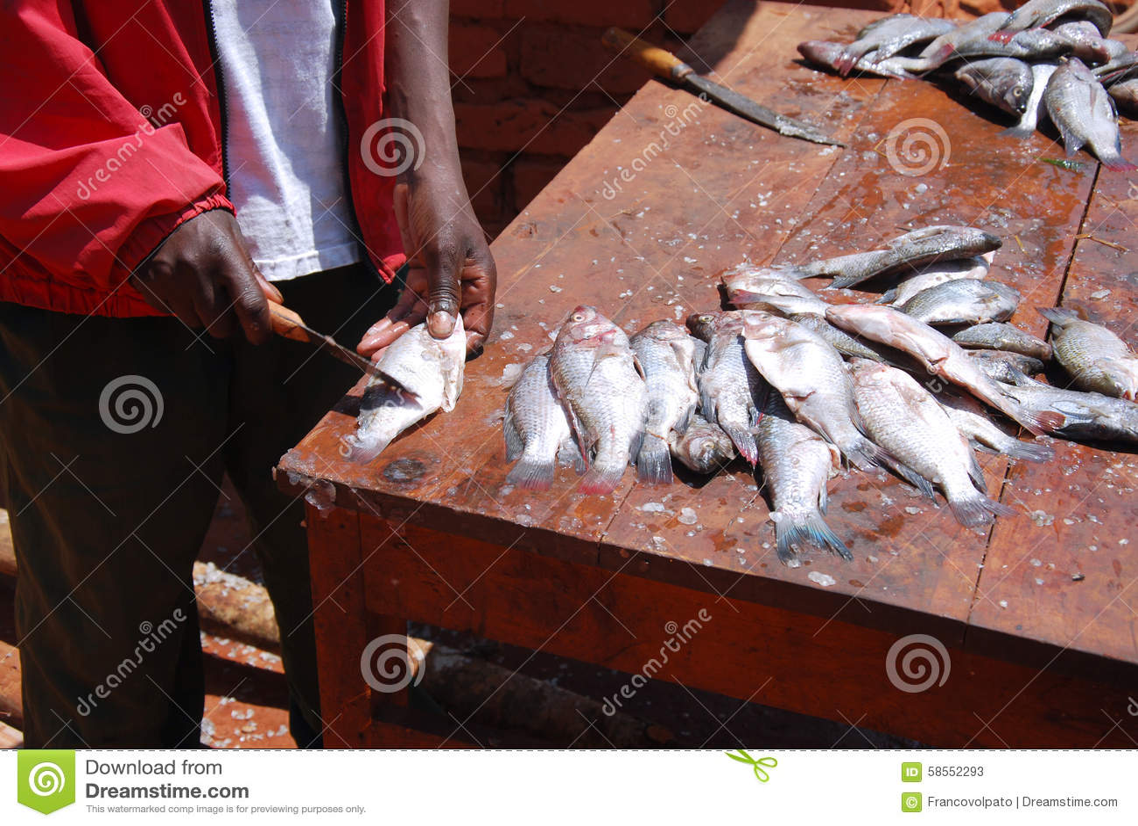 Уборщик рыб на рынке Pomerini в Танзании, Африке 72