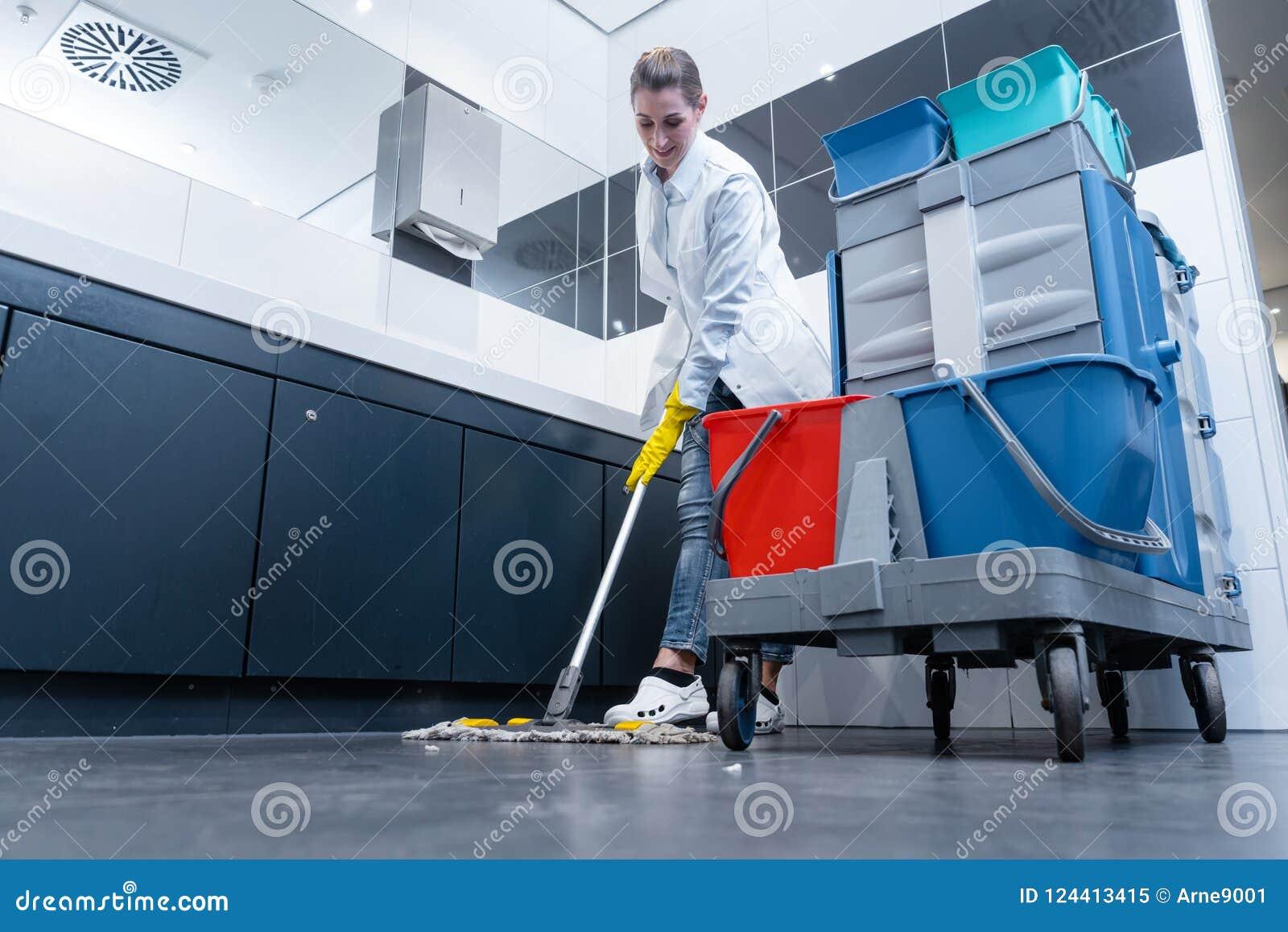 Уборщица mopping пол в уборном