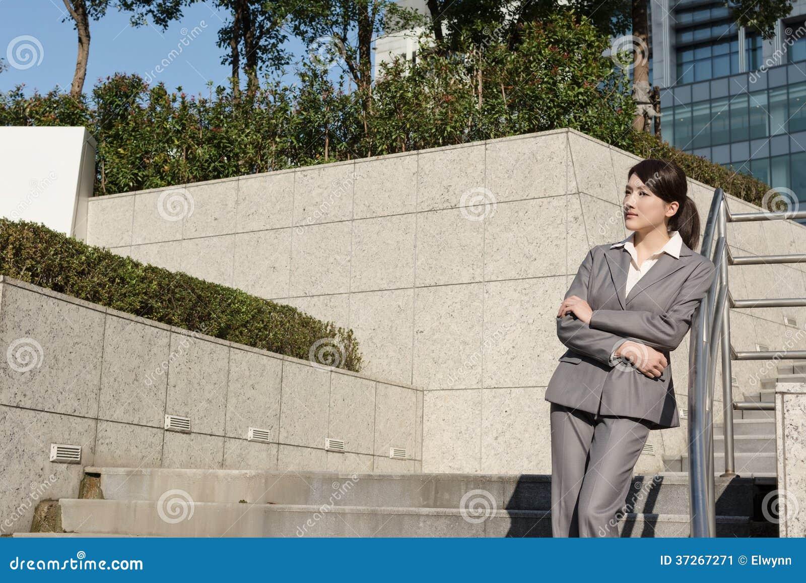Уверенно азиатская бизнес-леди стоя в вне офисе внутри