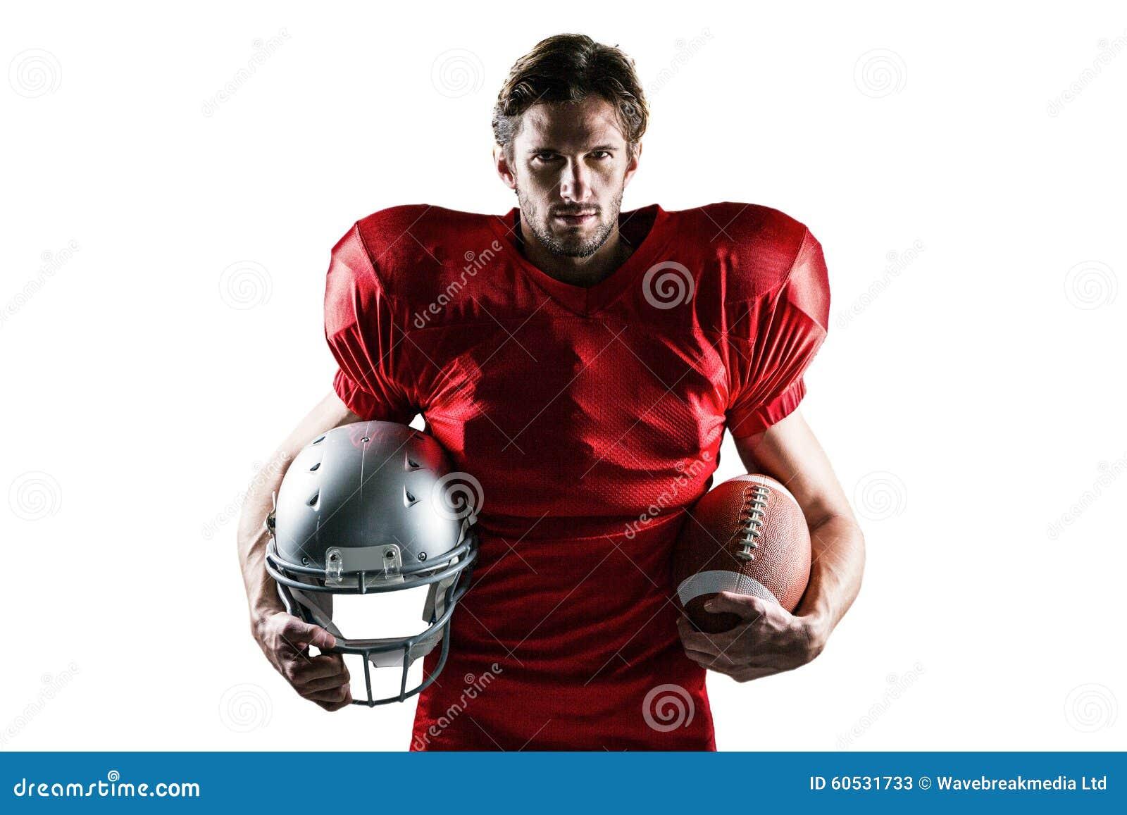 Уверенно американский футболист в красном jersey держа шлем и шарик