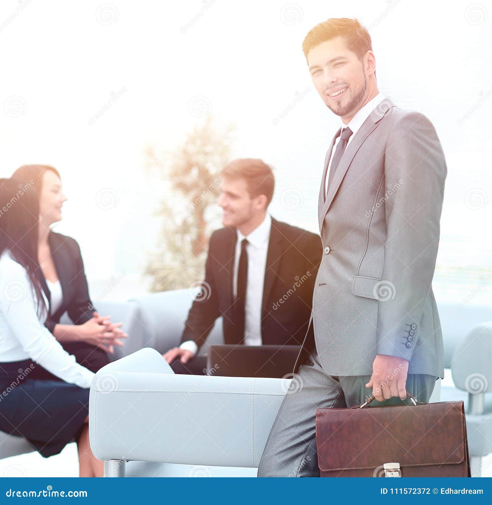 Уверенно бизнесмен при портфель стоя в лобби офиса