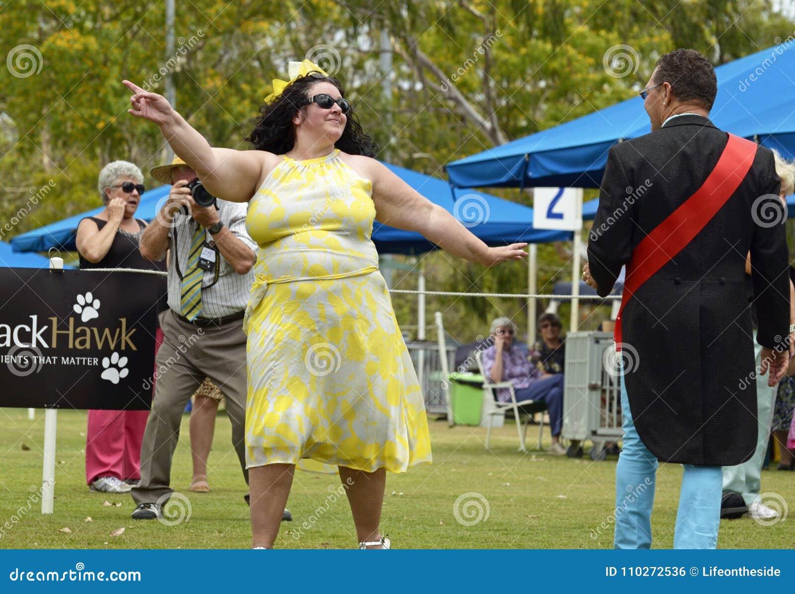 Уверенно, цветистый, потеха, счастливая женщина плюс-размера моделируя на выставке собак