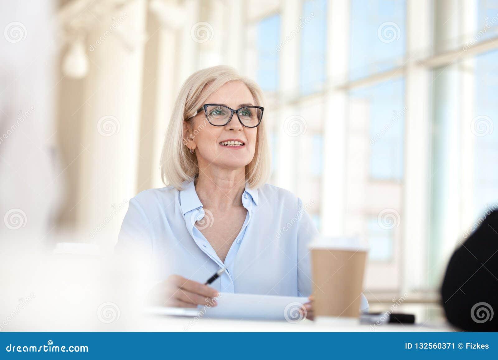 Уверенный зрелый тренер руководителя бизнес-леди говоря на встрече