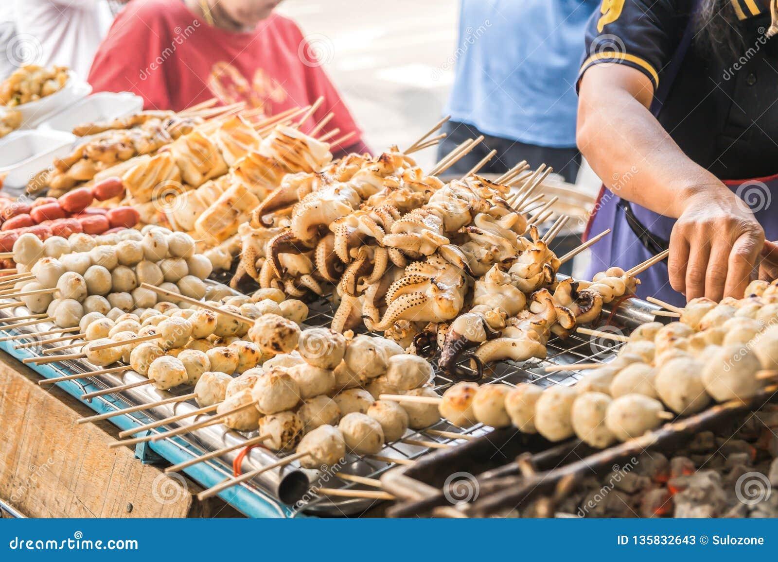 Уголь зажарил brochette еды для продажи на местном рынке в Бангкоке, Таиланде