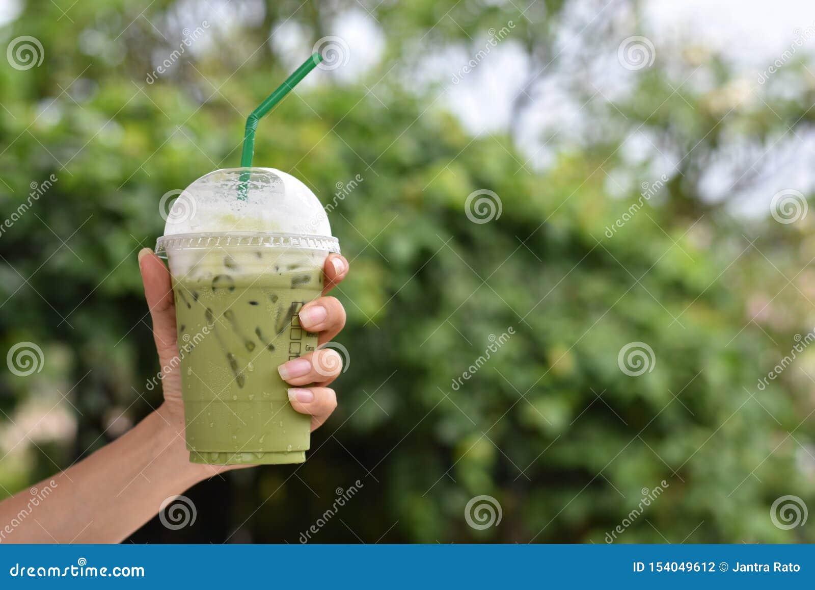 Удержание руки замороженного зеленого чая в пластиковом стекле