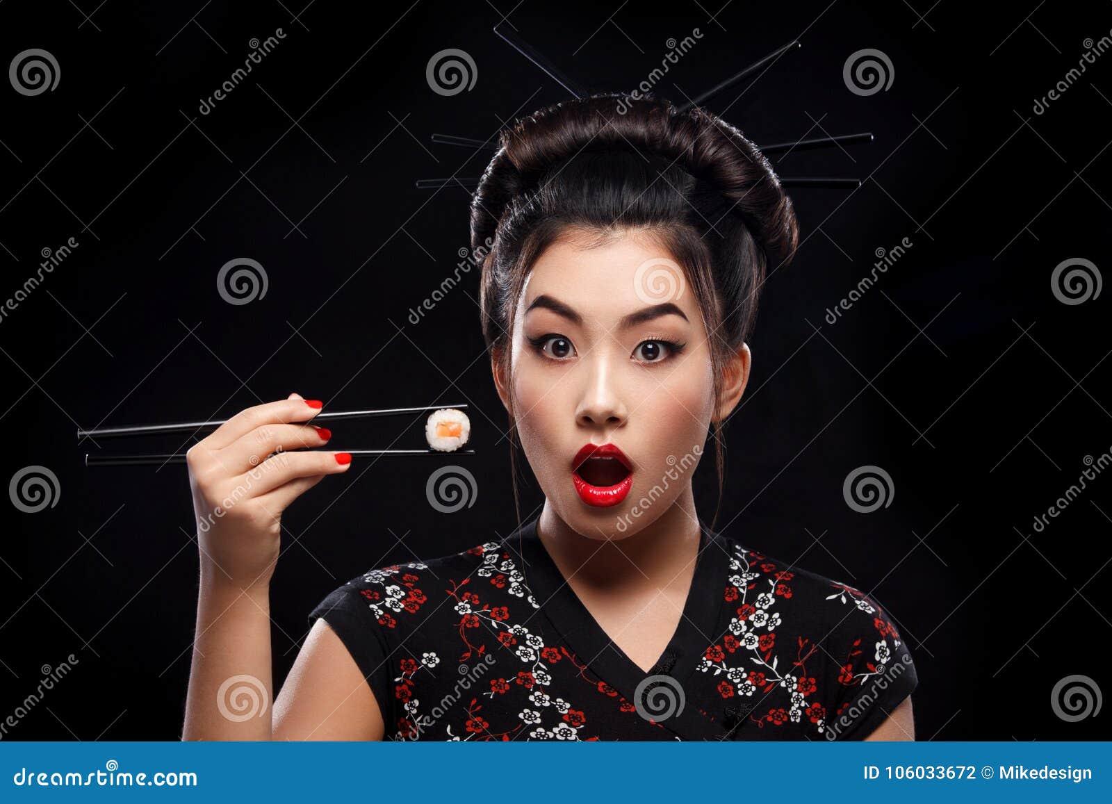 Удивленная азиатская женщина есть суши и крены на черной предпосылке