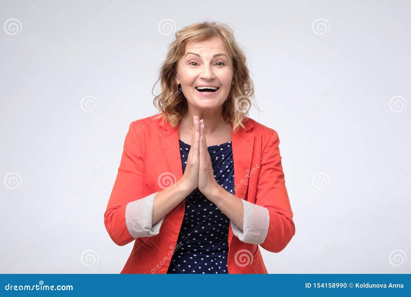 Удивленная зрелая женщина в красной куртке будучи в восторге о новостях смотря камеру