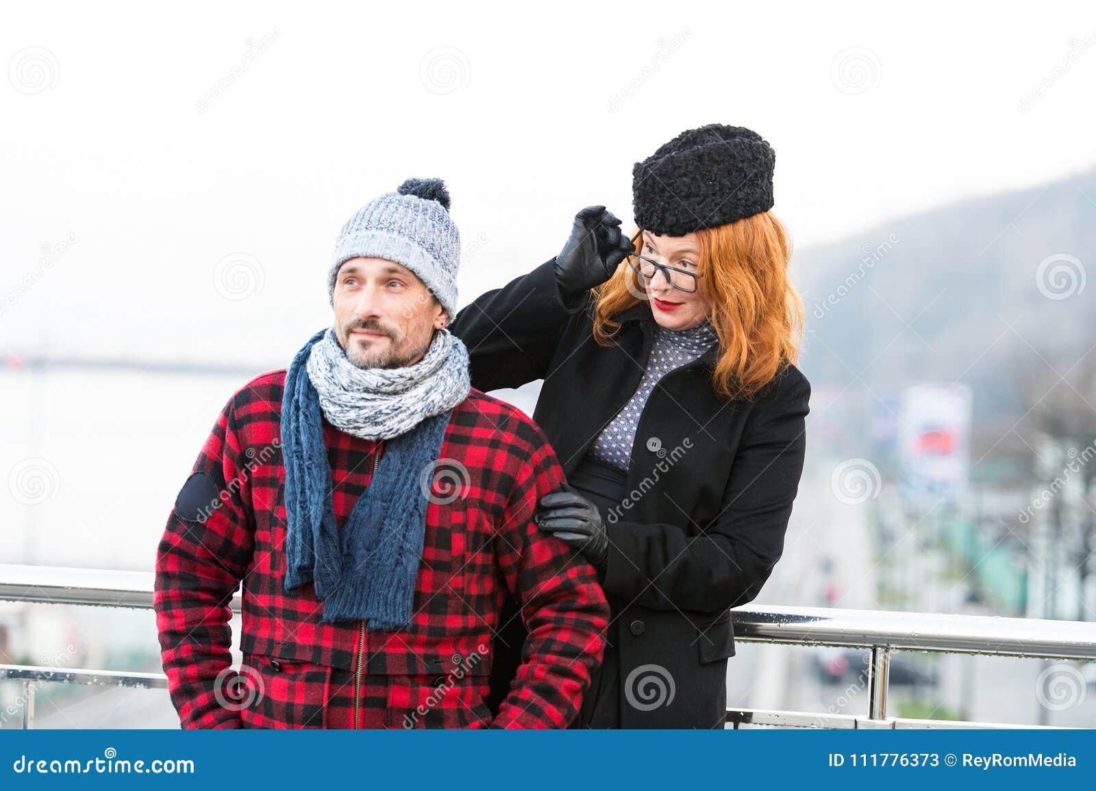 Удивленная красная женщина волос в стеклах посмотрела незнакомца на мосте Рассматривать женщины стекла от задней части человека