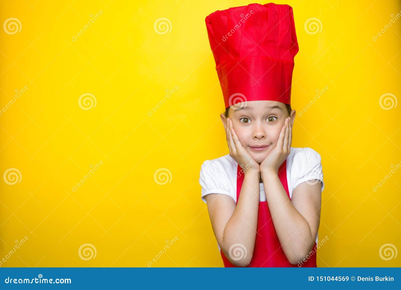 Удивленная маленькая девочка в костюме красного шеф-повара с руками на щеках на желтой предпосылке с космосом экземпляра