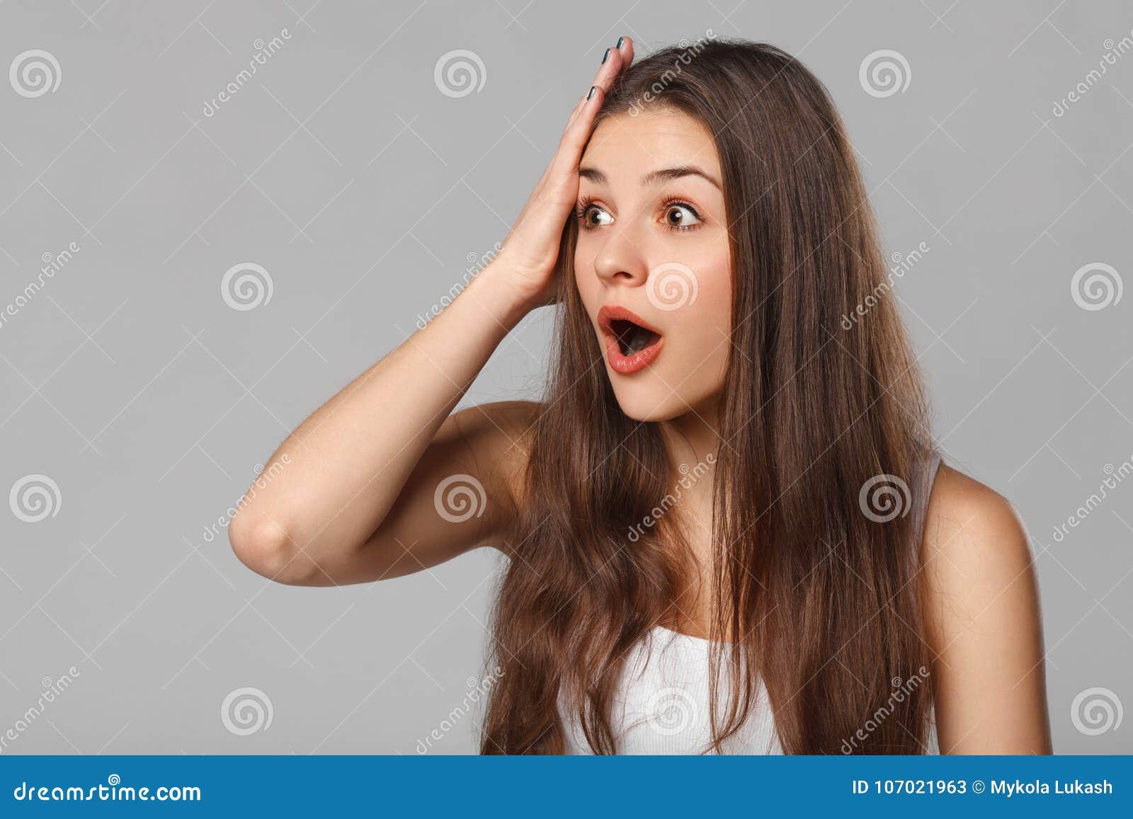 Удивленная счастливая женщина смотря косой в ободрении, изолированном на серой предпосылке