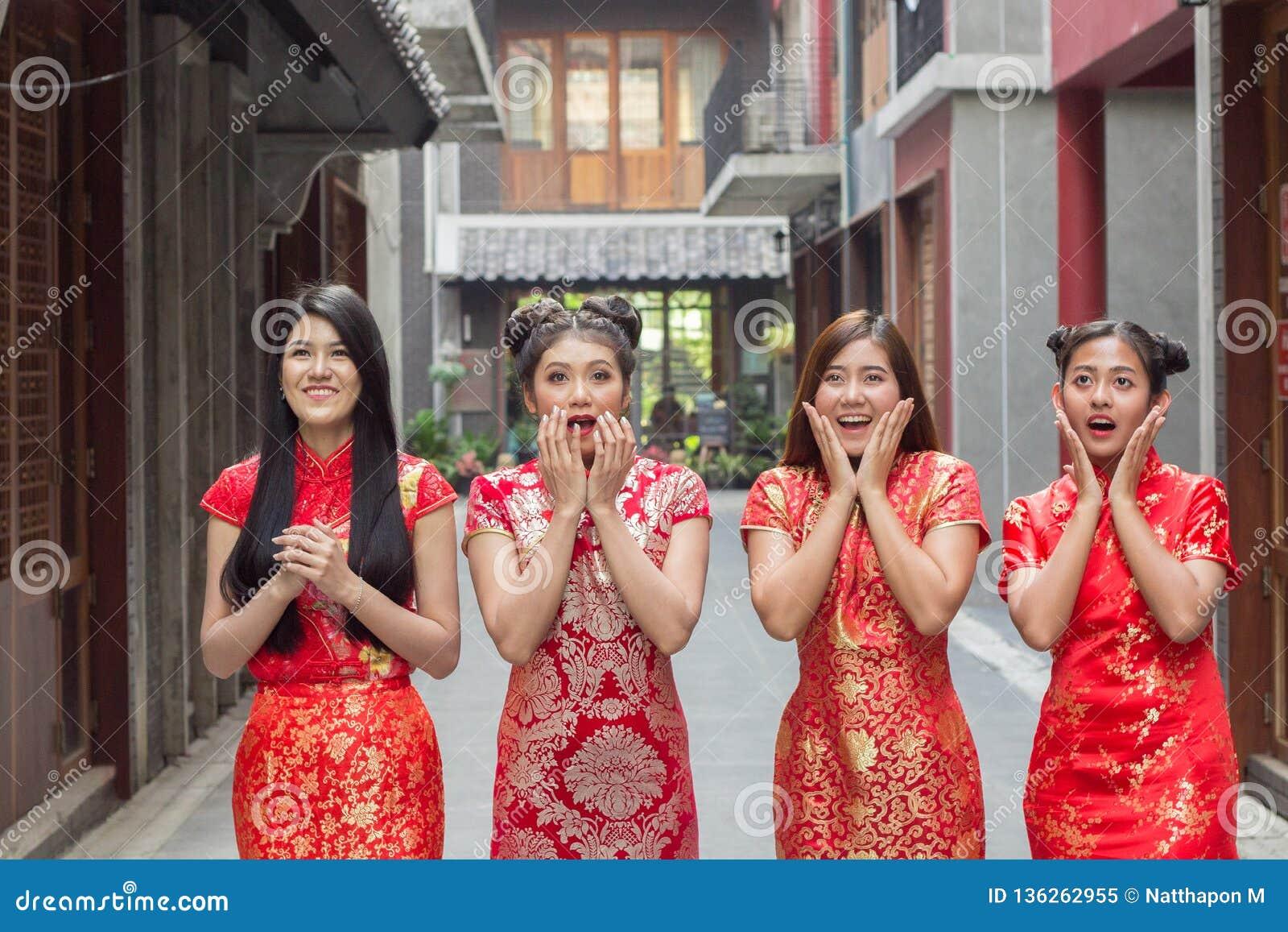 Удивленная счастливая красивая женщина смотря вверх в ободрении, группе в составе платье cheongsam женщины нося chainese смотря ч