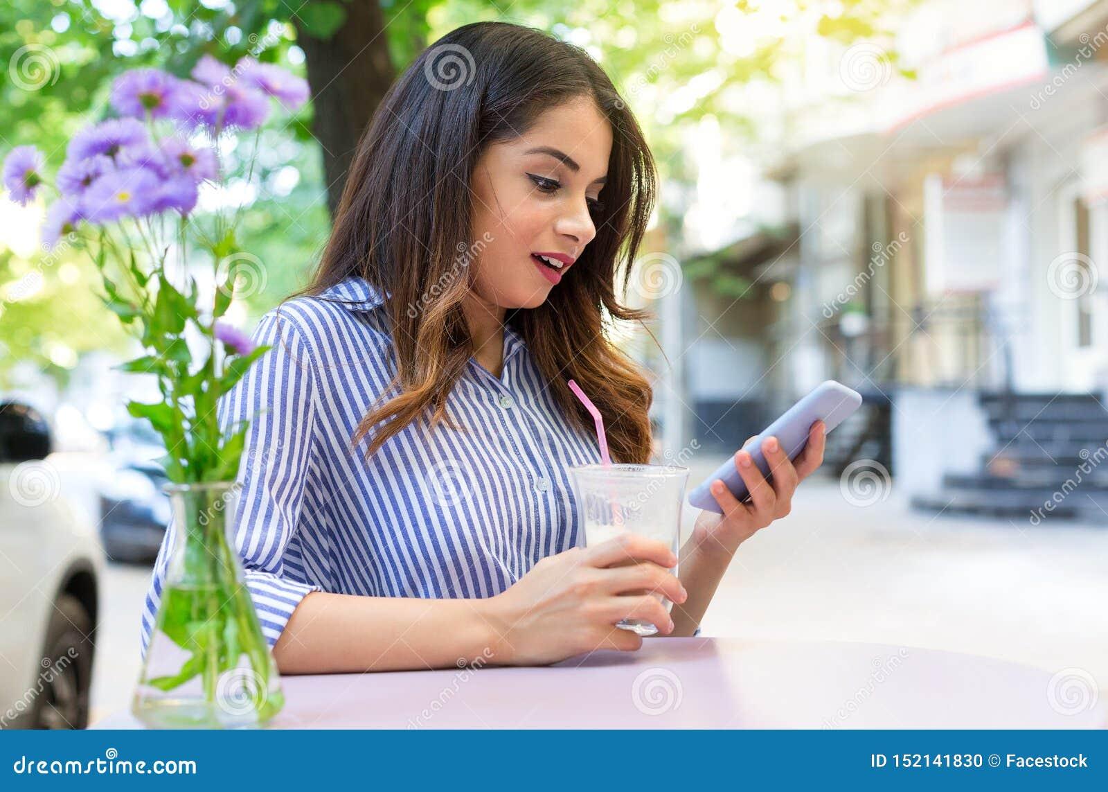 Удивленный кофе молодой женщины выпивая в кафе и смотреть телефон Космос экземпляра, на открытом воздухе