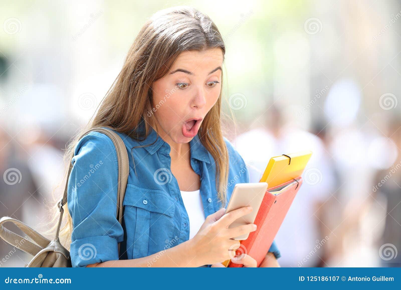 Удивленный студент получая хорошие онлайн новости
