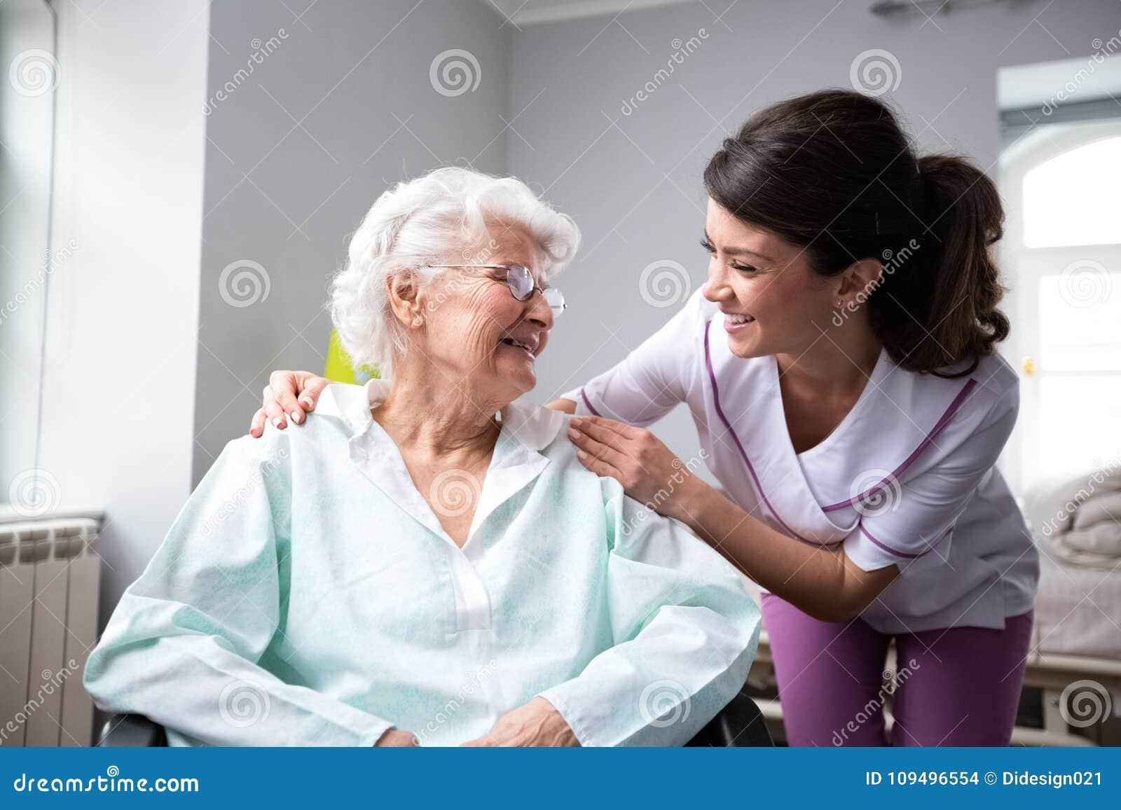 Удовлетворенный и счастливый старший пациент женщины с медсестрой