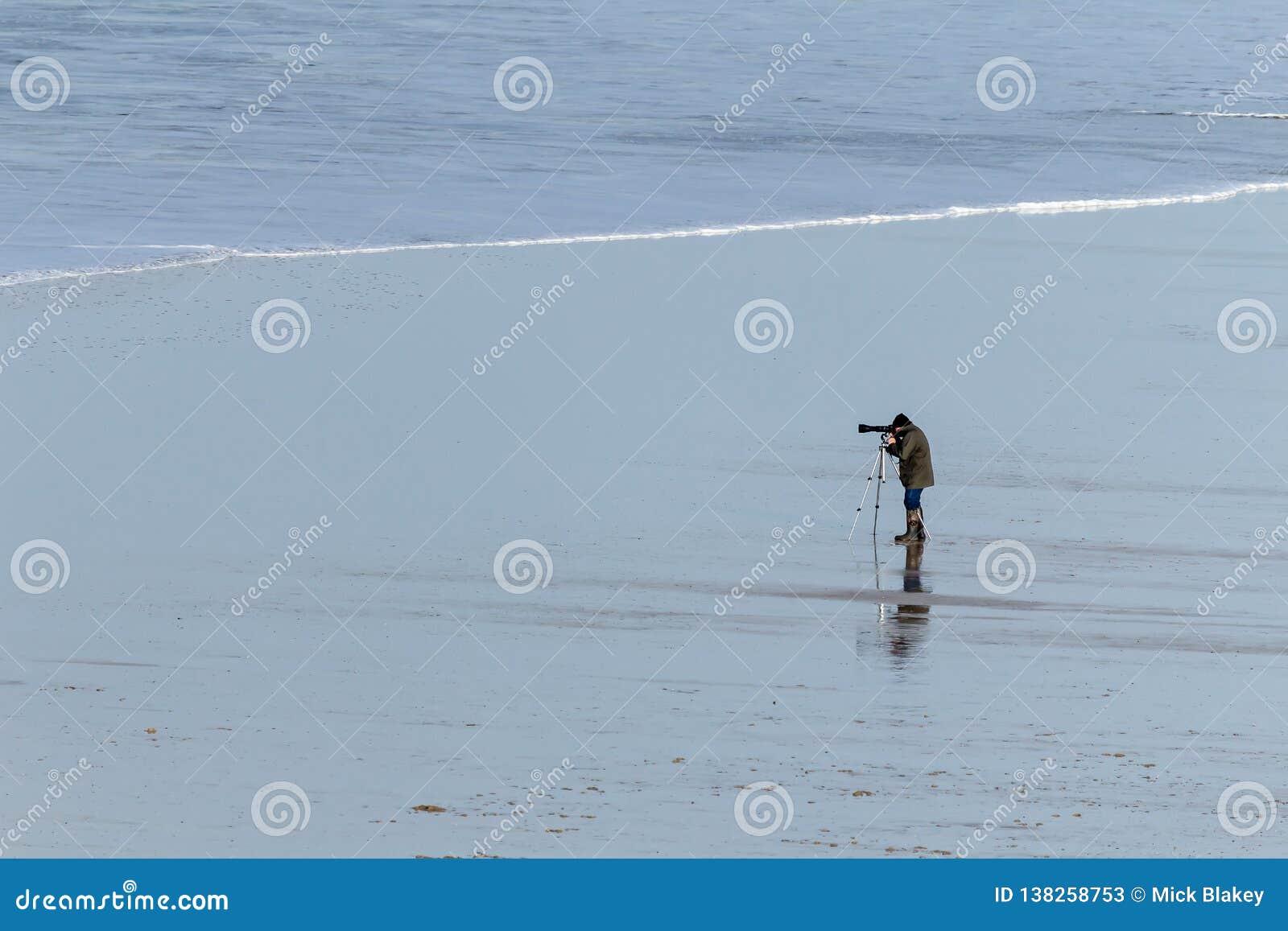 Уединенный фотограф на дезертированном пляже в северном Корнуолле