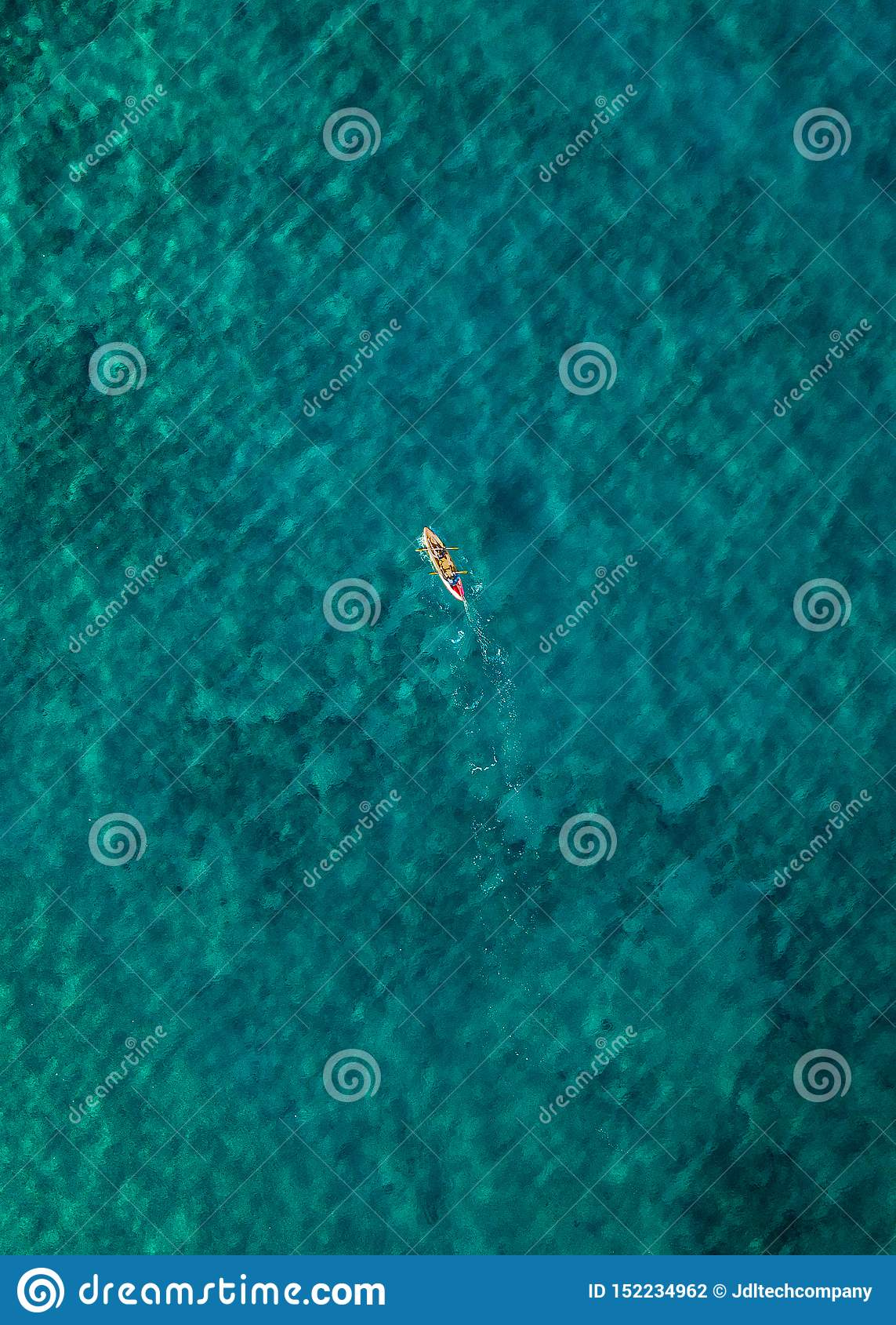 Уединенный человек сплавляясь на каяке в ясной воде teal