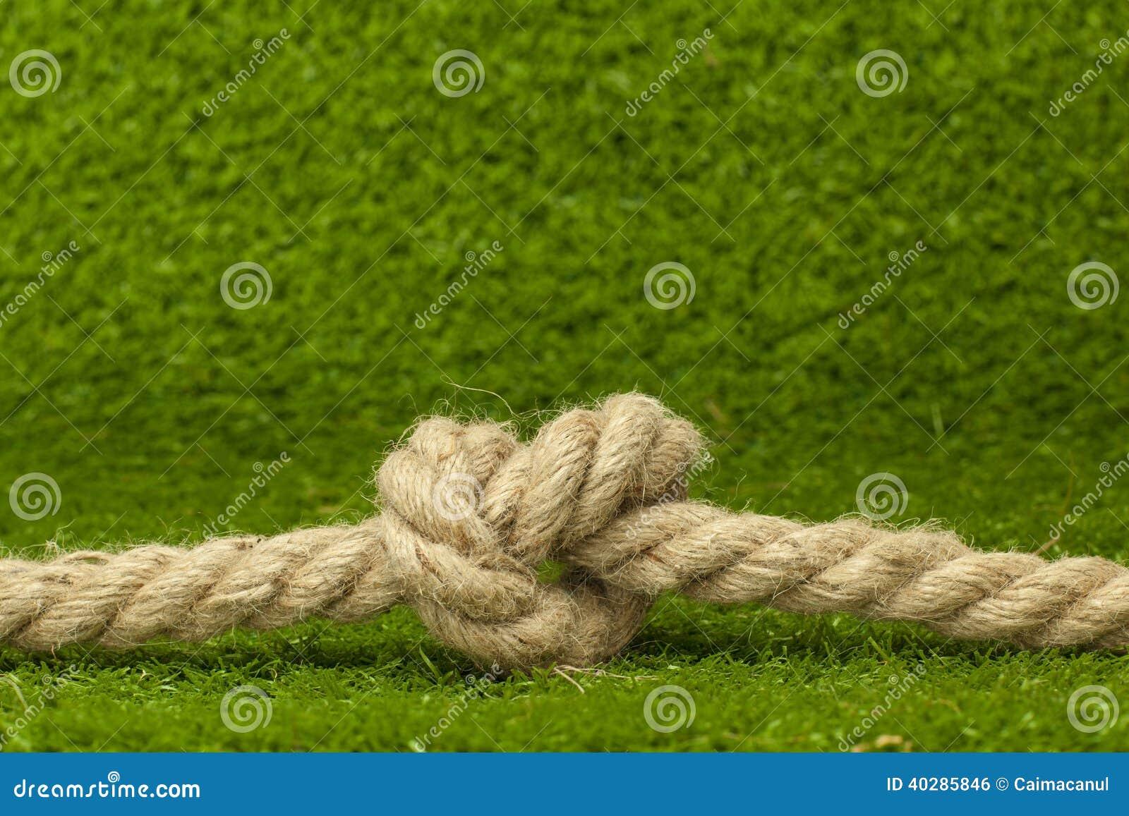 Узел на веревочке над зеленой травой