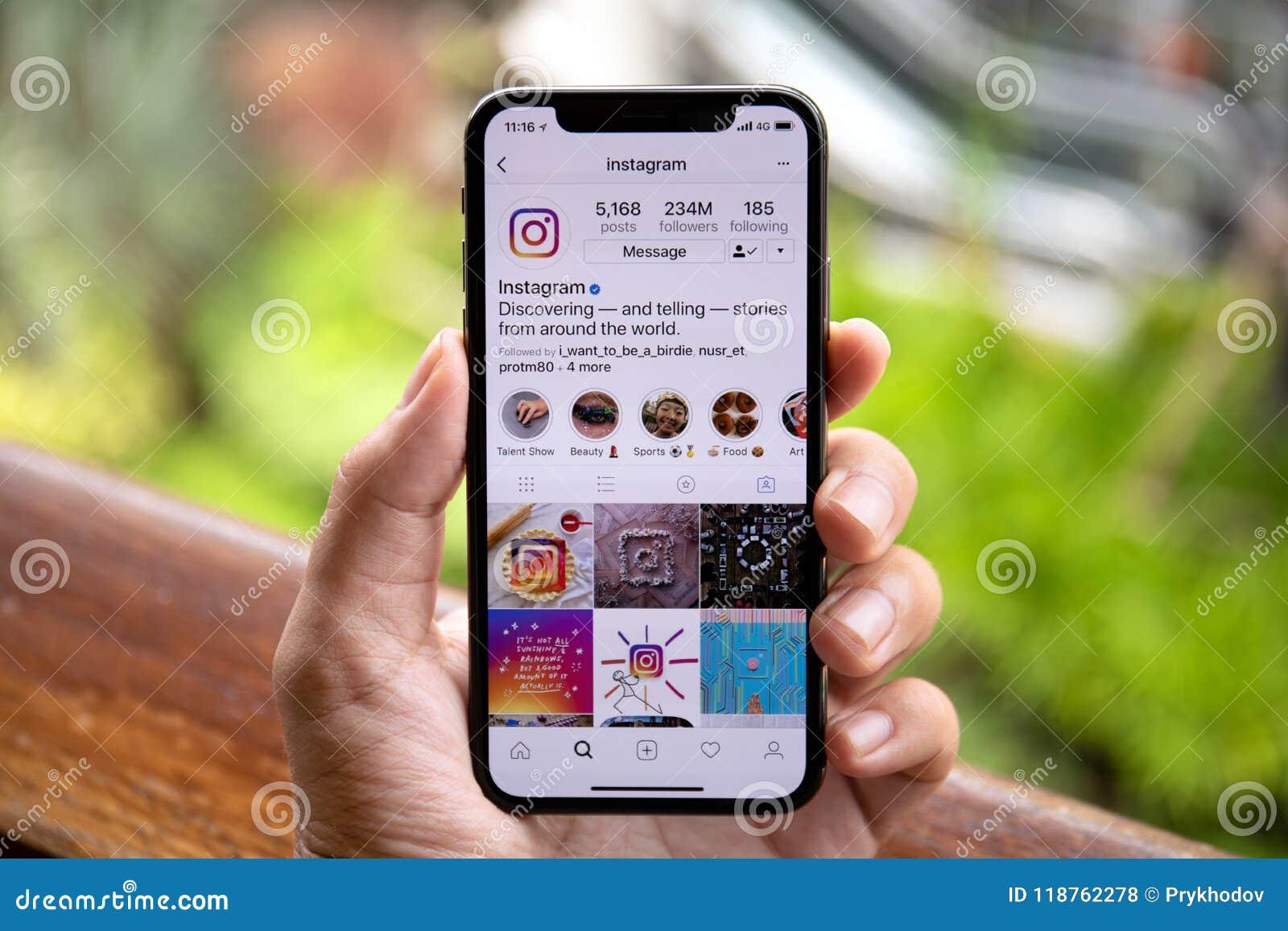 Укомплектуйте личным составом руку держа iPhone x с социальным обслуживанием Instagr сети