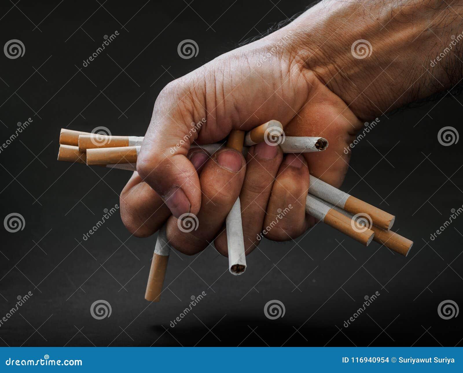 Укомплектуйте личным составом удерживание руки и разрушьте сигареты на черной предпосылке Qui