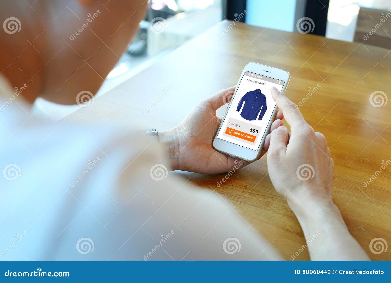 Укомплектуйте личным составом держать smartphone с выберите рубашку на вебсайте ecommerce