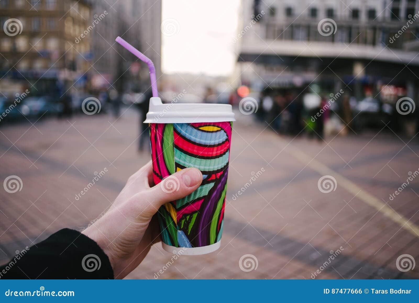 Укомплектуйте личным составом руку ` s держа яркий цвет и бумажный стаканчик кофе на предпосылке города