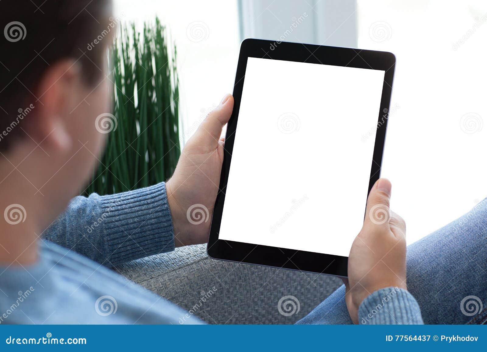 Укомплектуйте личным составом сидеть на софе держа планшет с изолированным экраном