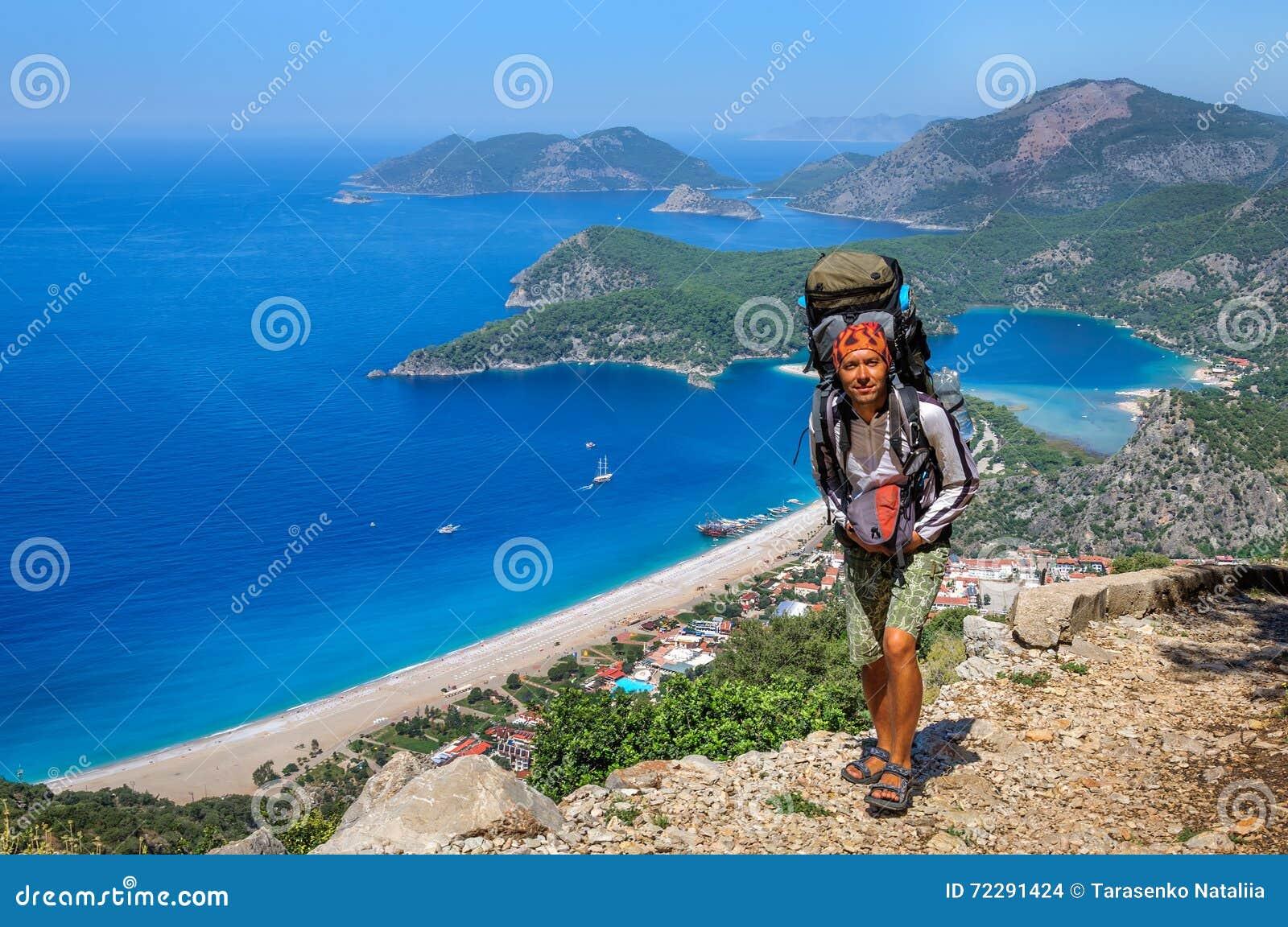 Download Укомплектуйте личным составом с большим рюкзаком A на море дороги Стоковое Фото - изображение насчитывающей пляжа, человек: 72291424