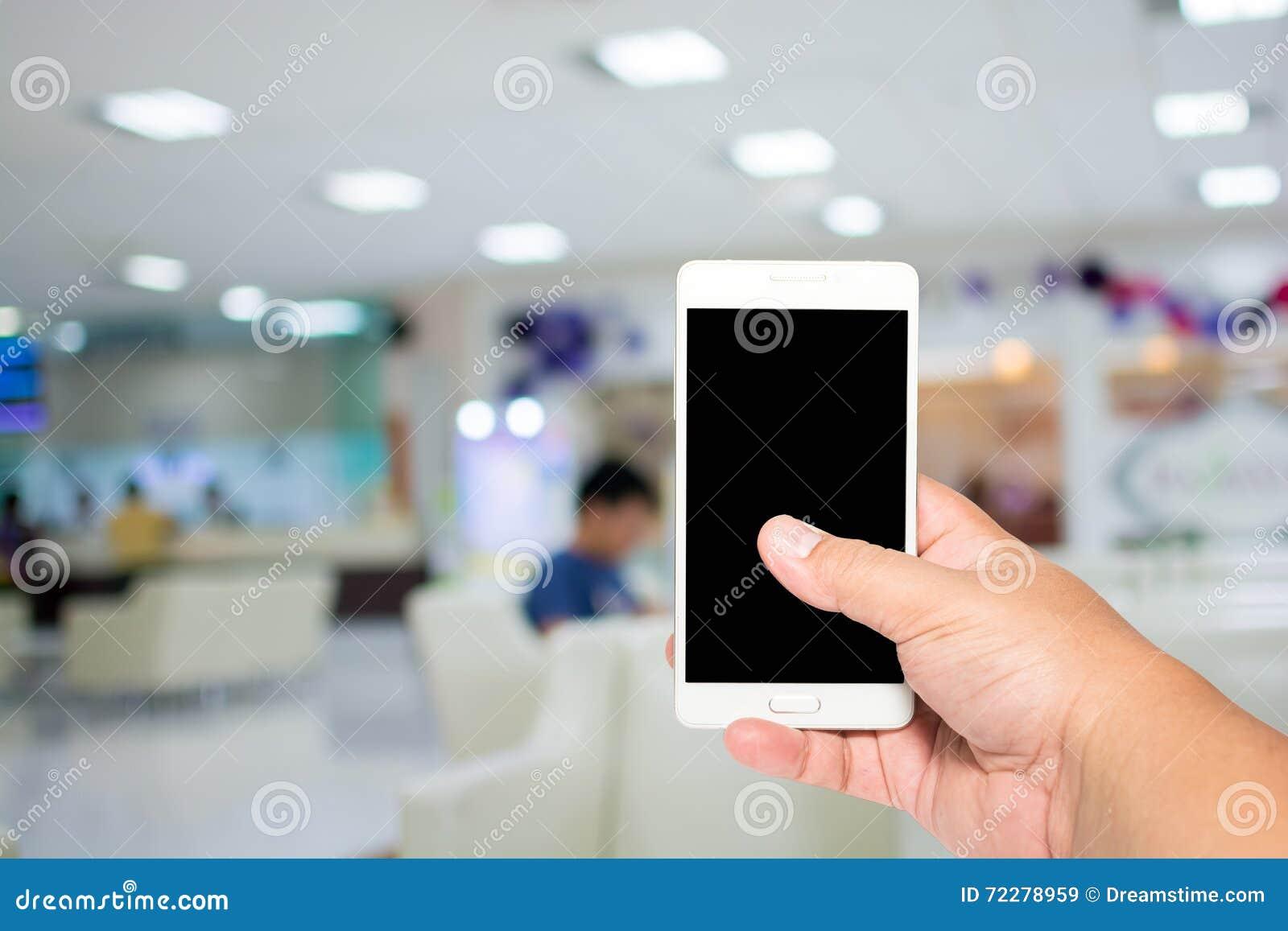 Download Укомплектуйте личным составом телефон владением умный на лобби для того чтобы увидеть предпосылку доктора Стоковое Изображение - изображение насчитывающей этническо, толпа: 72278959