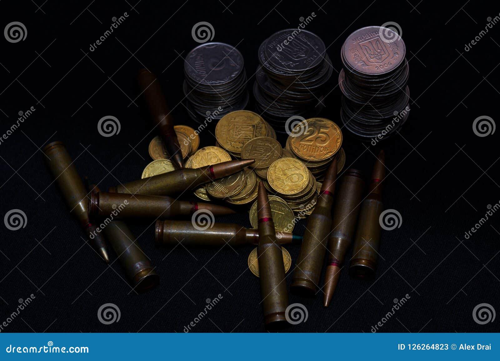 Украинские малые монетки с боеприпасами винтовки воинскими на черной предпосылке Символизирует войну для денег