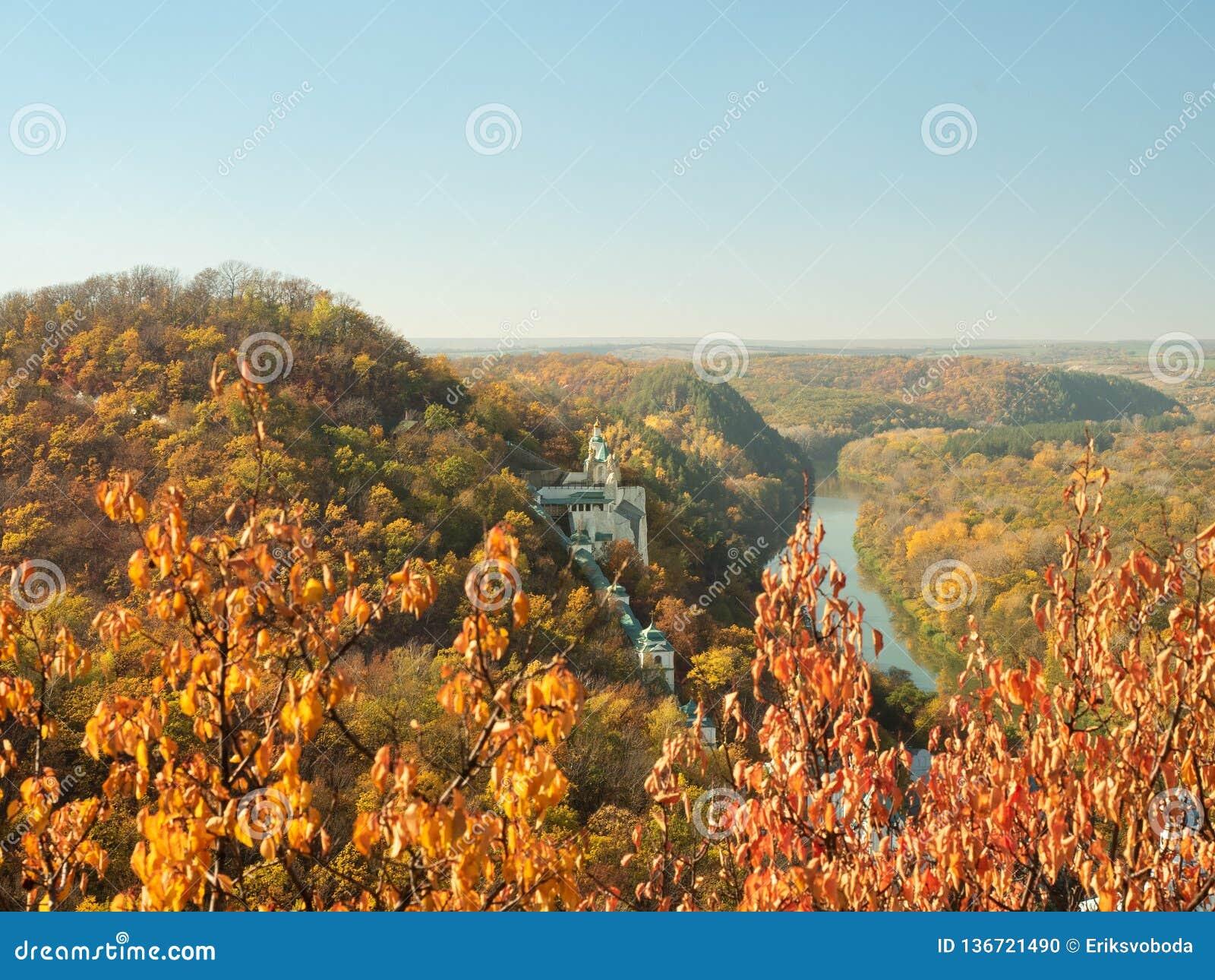 Украинский ландшафт природы Скит на холме Узкое река пропуская под холмами Красочный лес осени на холмах