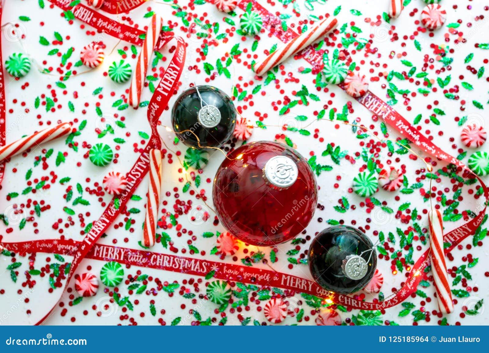 Украшение с красной жидкостью заполнило шарик орнамента рождества и 2 зеленых заполненных шарика орнамента окруженного красным цв