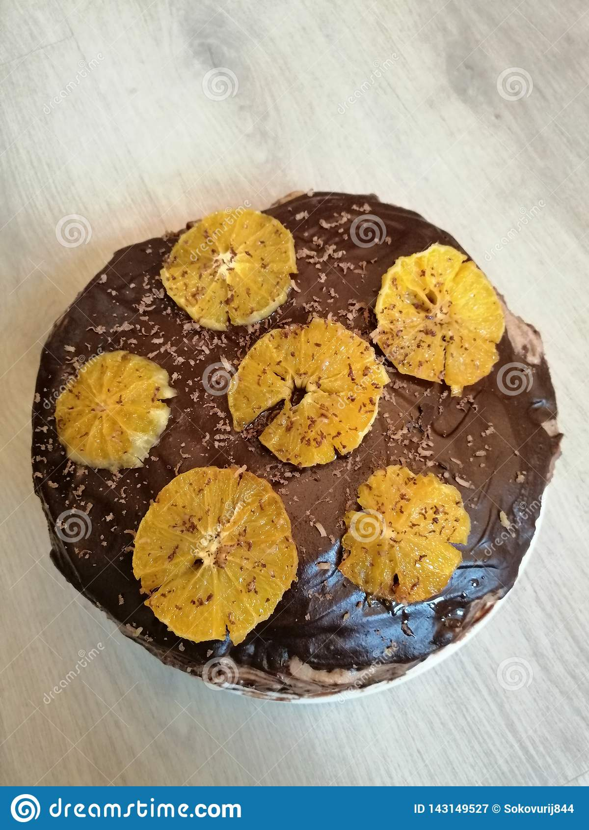 Украшенный шоколадный торт с апельсинами на доске