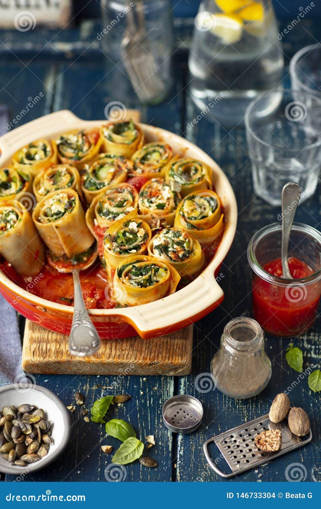 Улитки макаронных изделий сделали с лазаньей и заполненный с сыром шпината и фета