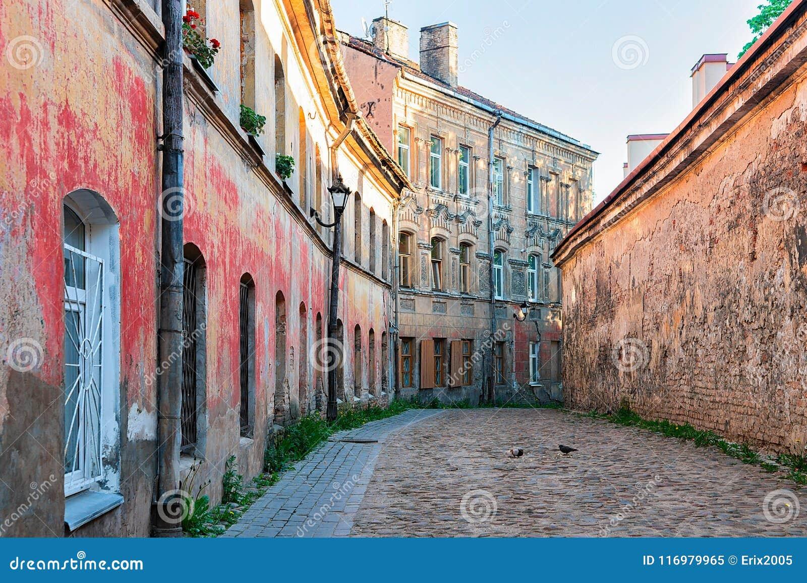 Улица со старыми домами и городом Вильнюсом Литвой булыжника старым