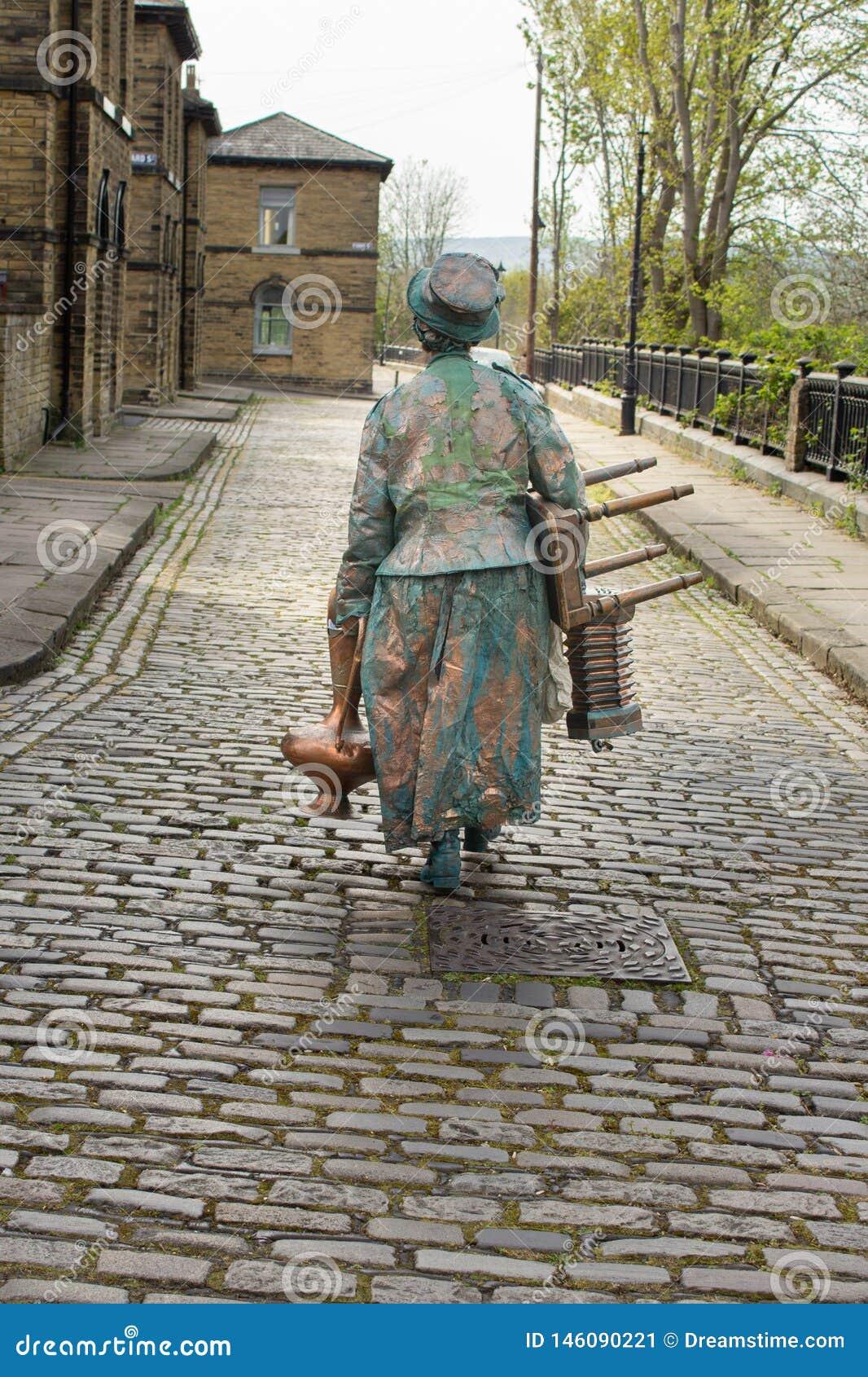 Уличный исполнитель делает ее путь дом над мостит булыжником
