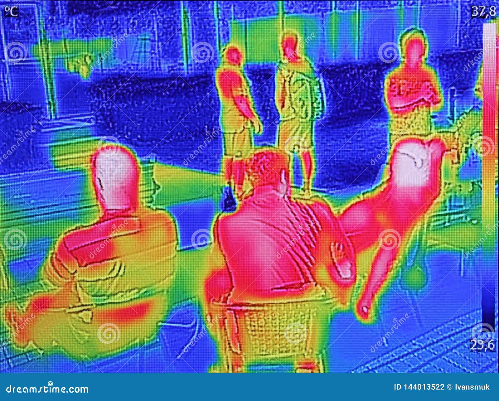 Ультракрасный показ изображения thermovision когда люди сидят на таблице