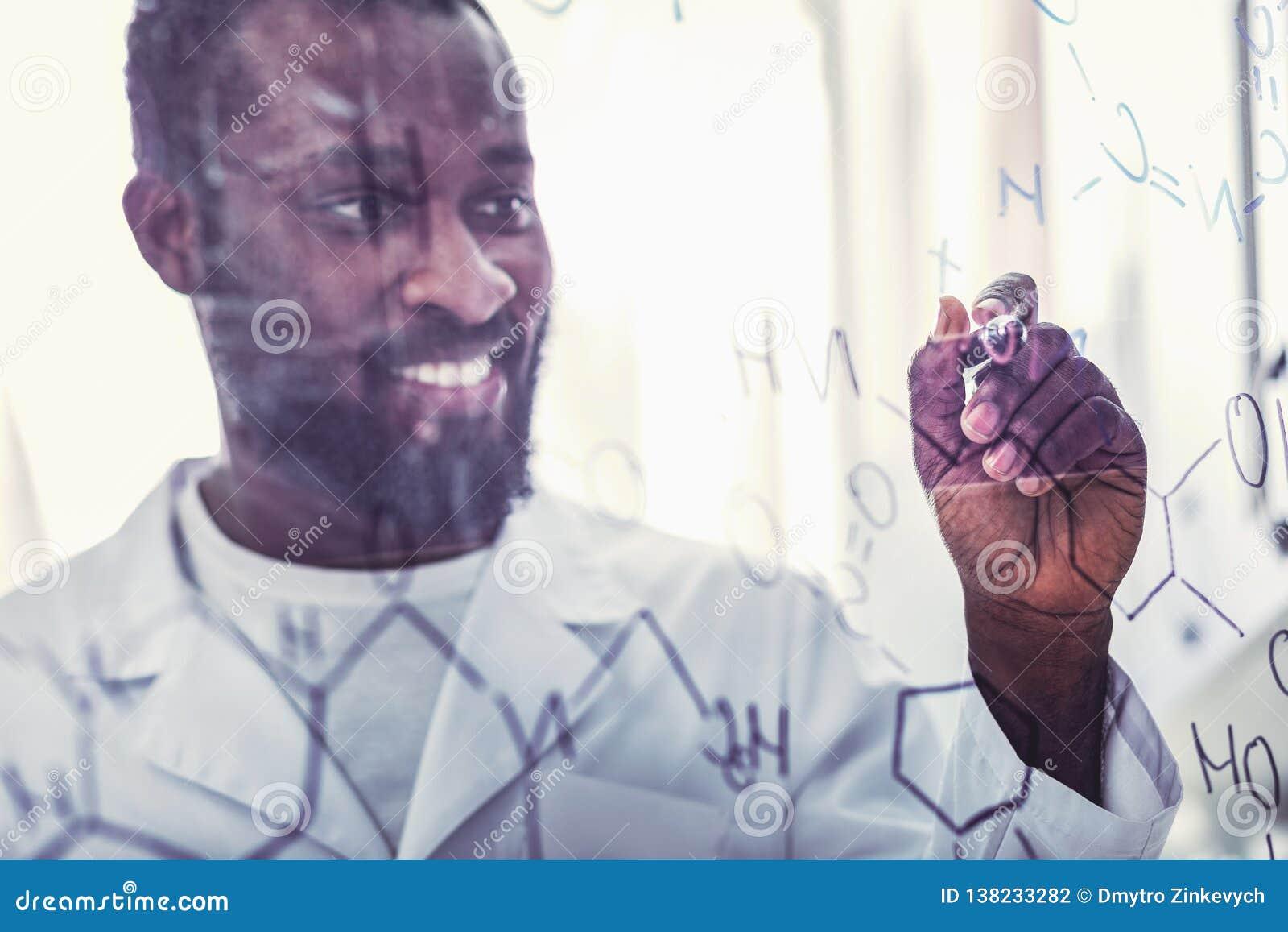 Умелое молодое химическое ассистентское положение около стеклянной доски