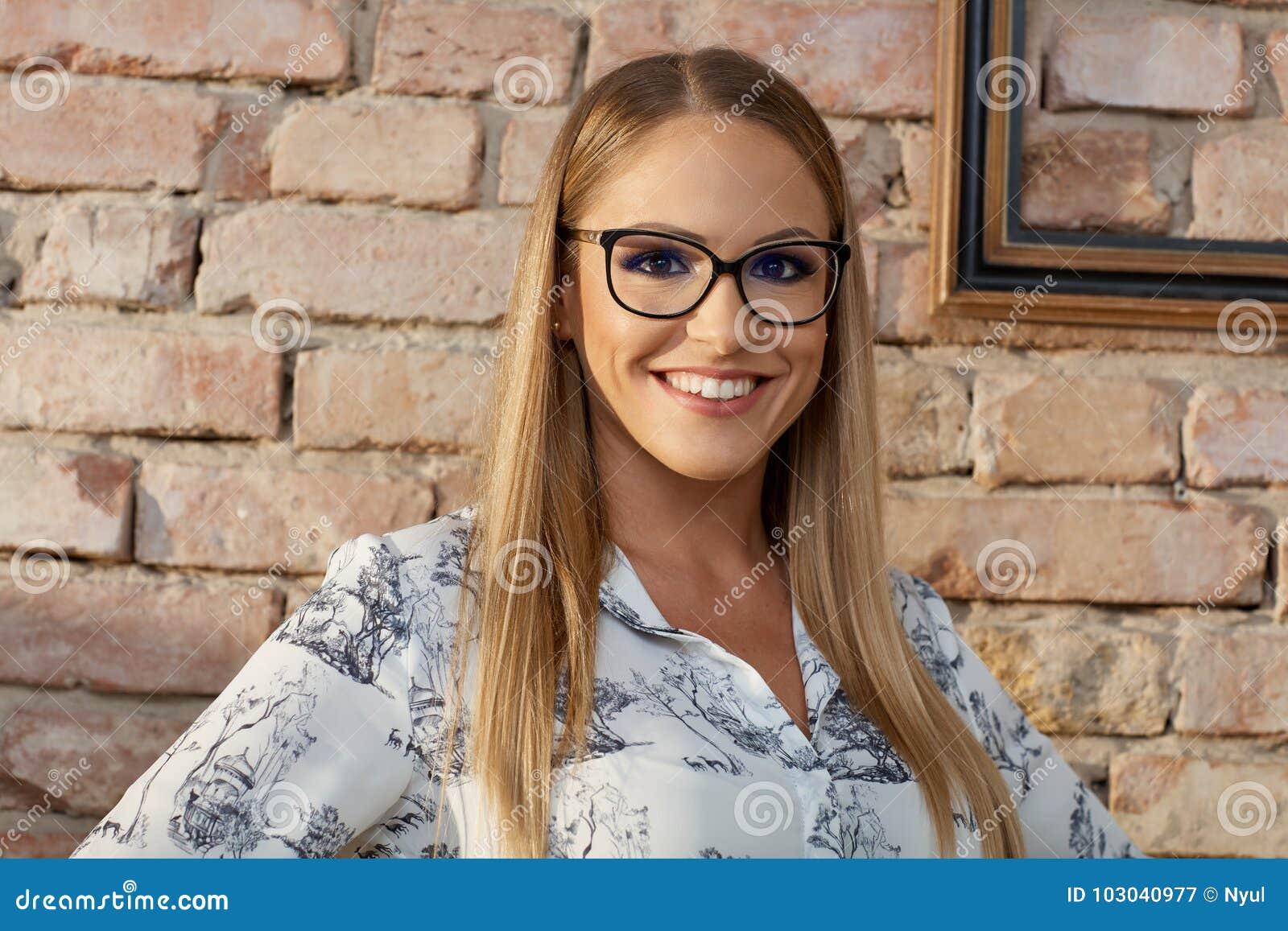 Умная молодая женщина в усмехаться стекел