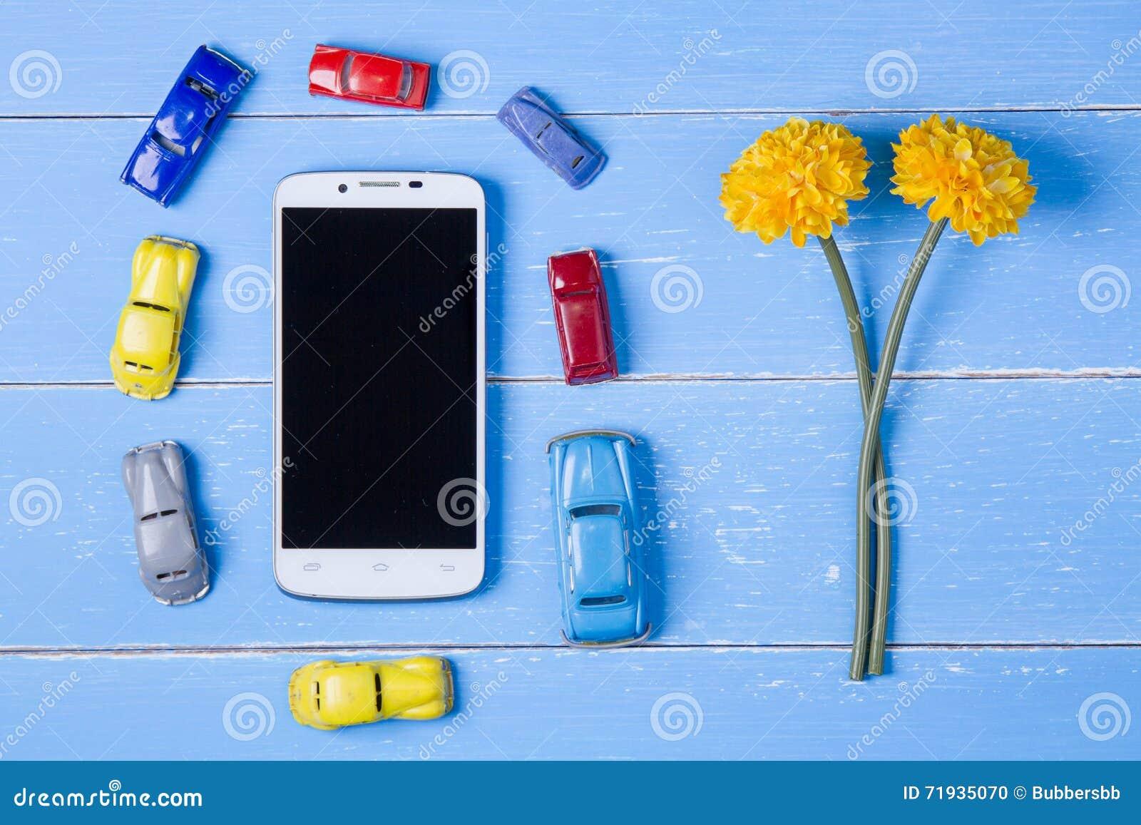 умные телефон, игрушки автомобиль и цветки пластмассы на голубом деревянном bac