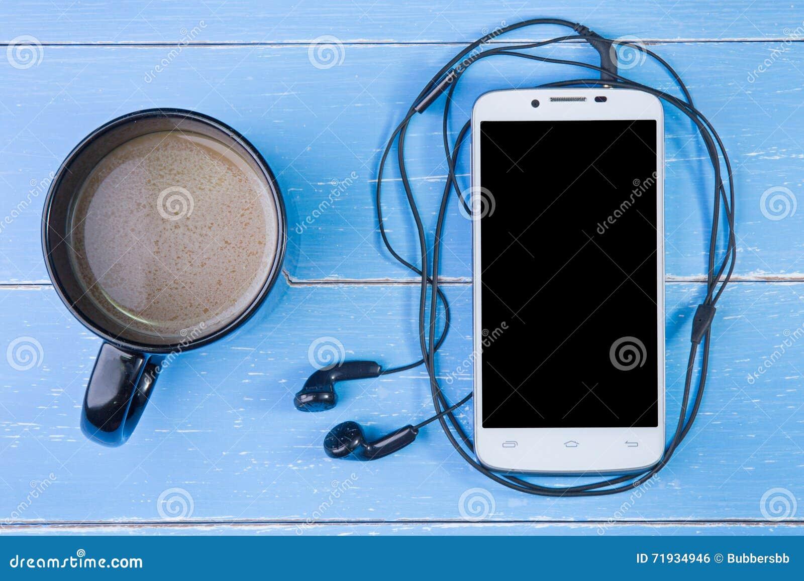 Умные телефон, наушник и кофейная чашка на голубом деревянном backgrou
