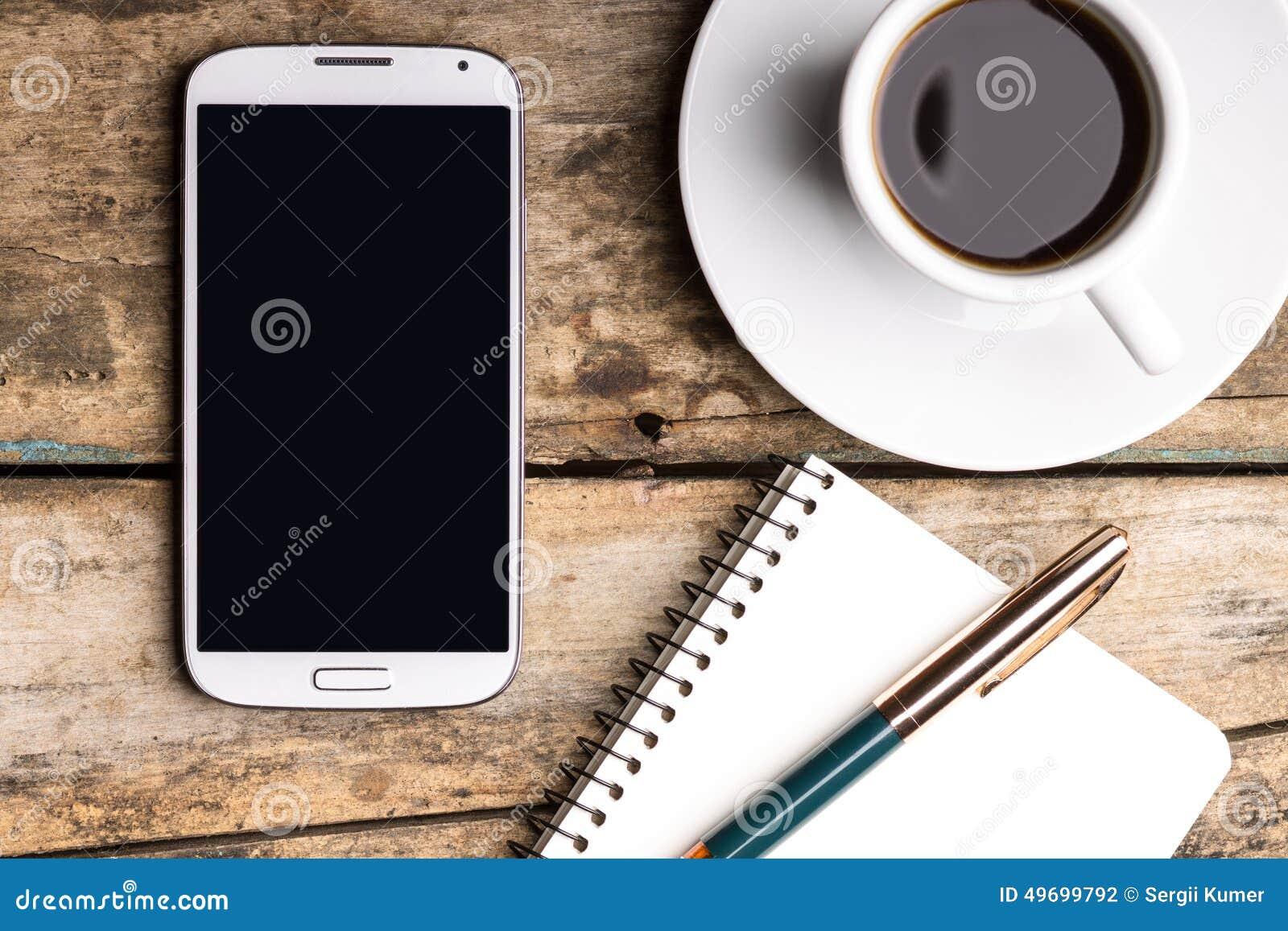 Умный телефон с тетрадью и чашкой сильного кофе