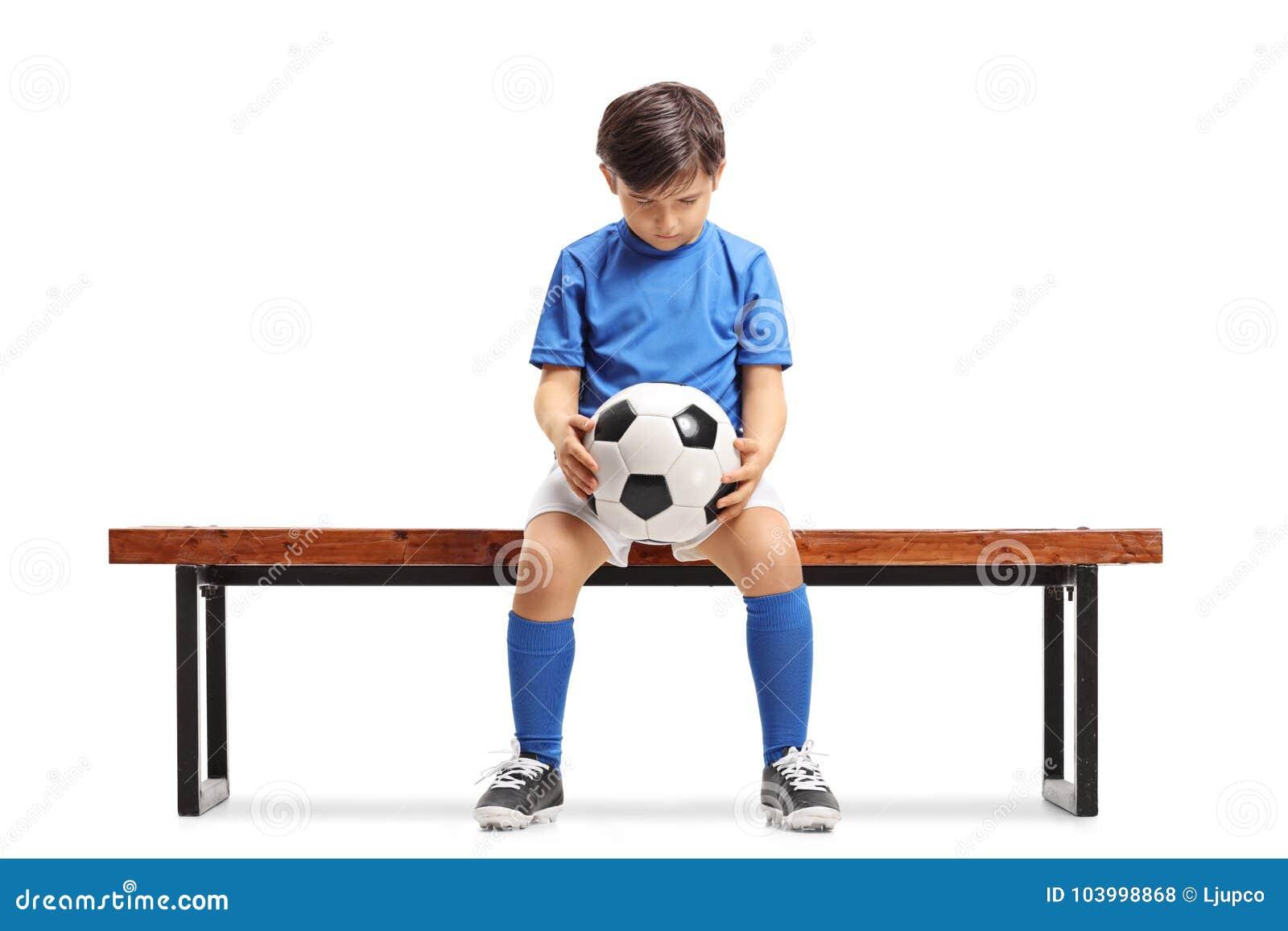 Унылый маленький футболист усаженный на деревянную скамью